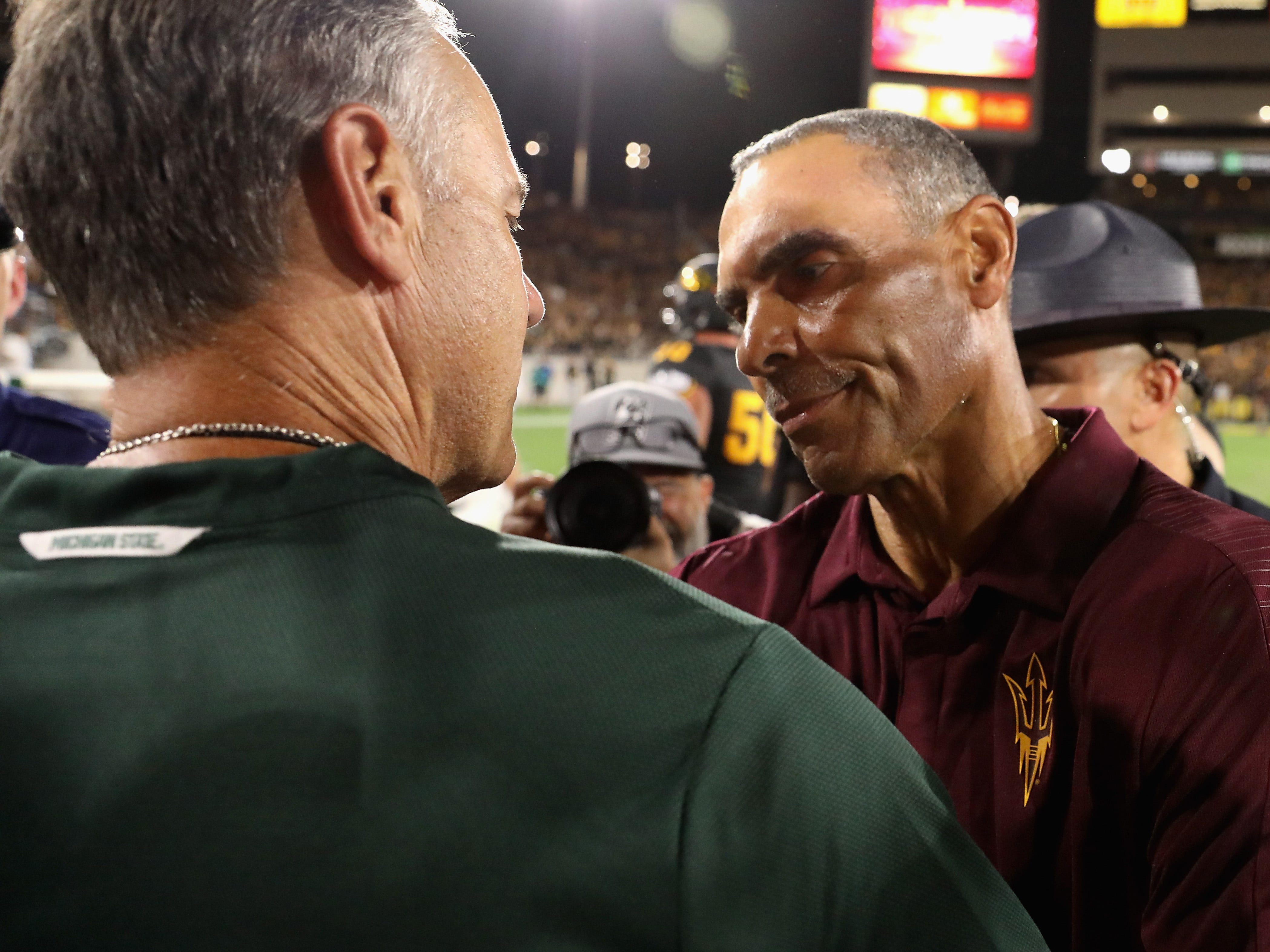 Head coach Herm Edwards (R) of the Arizona State Sun Devils greets head coach Mark Dantonio of the Michigan State Spartans following the college football game at Sun Devil Stadium on September 8, 2018 in Tempe, Arizona.  The Sun Devils defeated the Spartans 16-13.