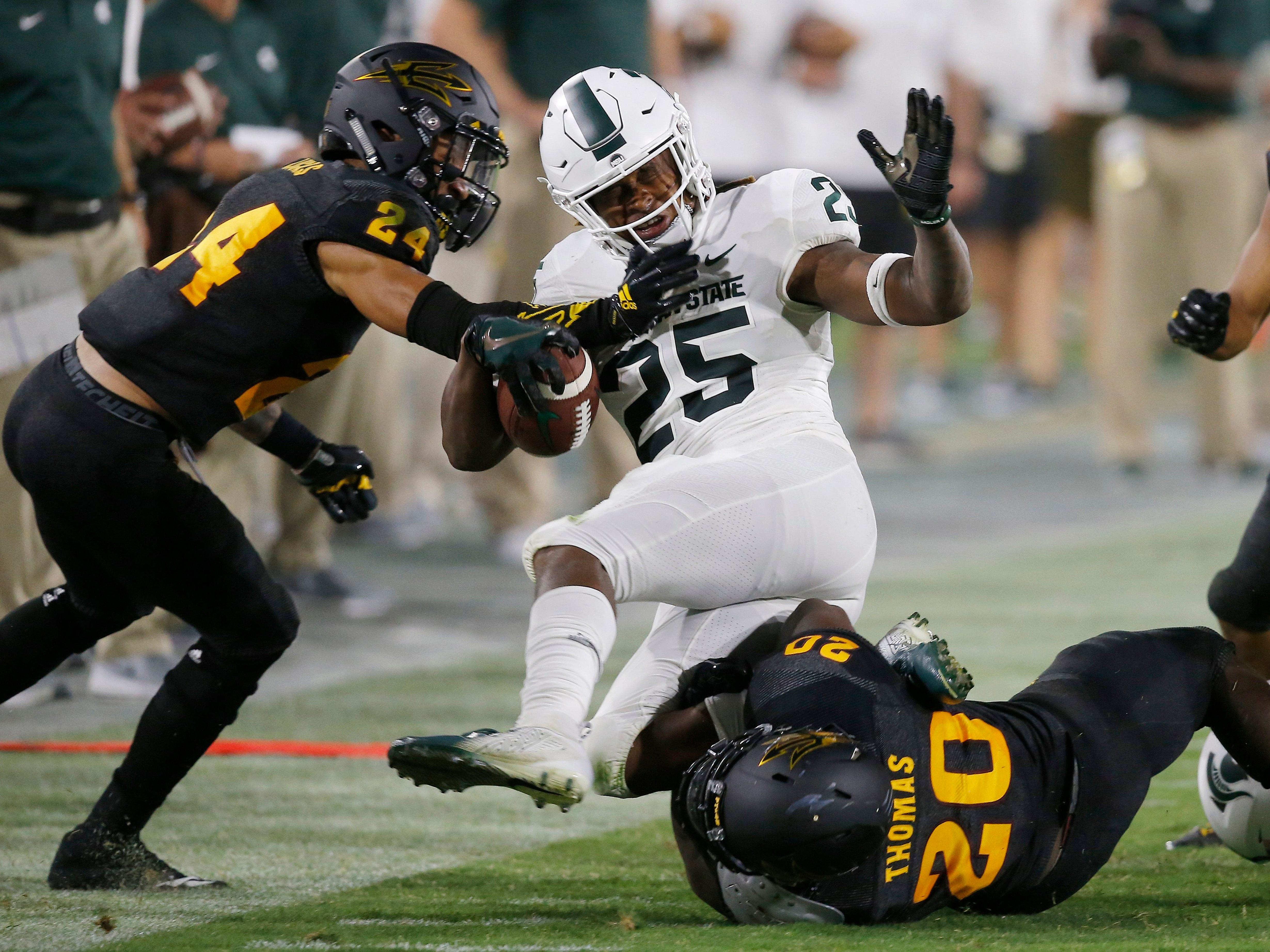 Michigan State wide receiver Darrell Stewart Jr. (25) gets tackled by Arizona State defensive back Chase Lucas (24) and linebacker Khaylan Kearse-Thomas (20) during the second half of an NCAA college football game Saturday, Sept. 8, 2018, in Tempe, Ariz. Arizona State defeated Michigan State 16-13.