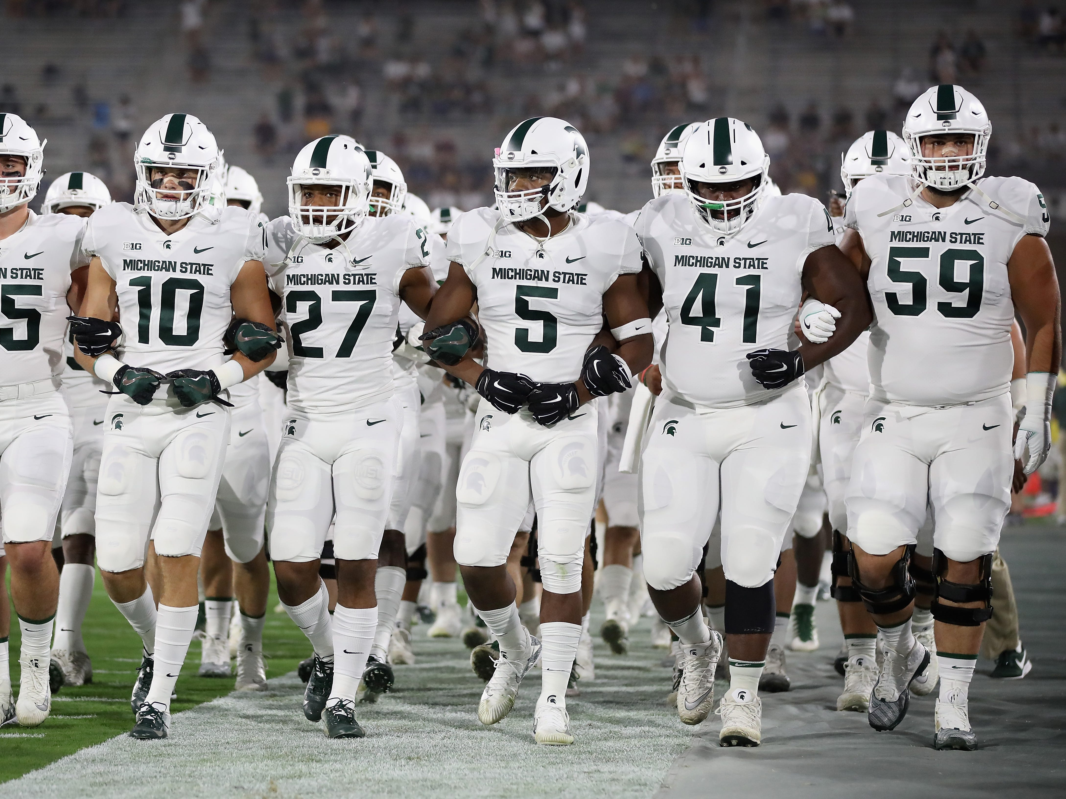 TEMPE, AZ - SEPTEMBER 08:  The Michigan State Spartans walk arm in arm onto the field before the college football game against the Arizona State Sun Devils at Sun Devil Stadium on September 8, 2018 in Tempe, Arizona.  (Photo by Christian Petersen/Getty Images)