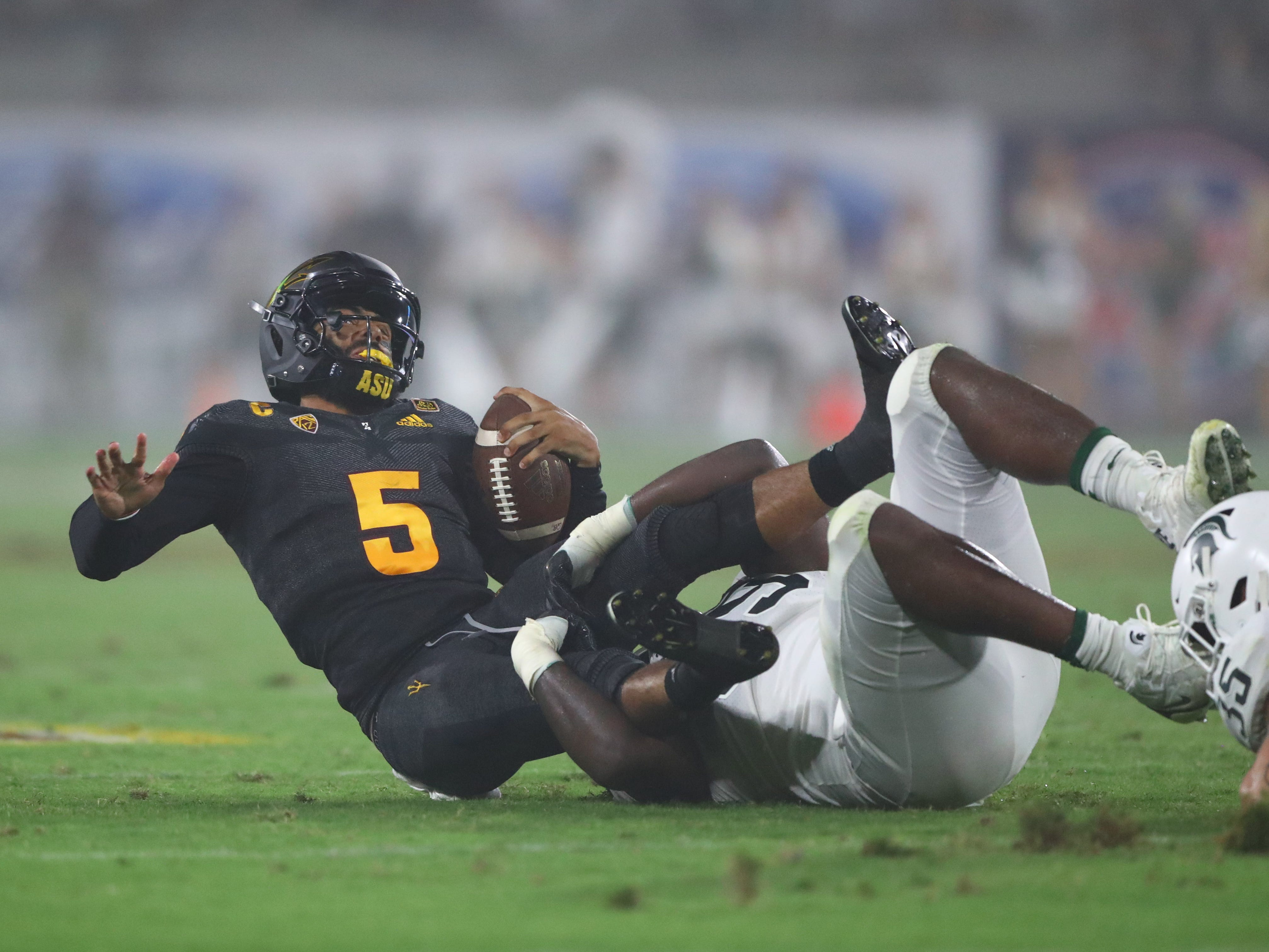 Arizona State Sun Devils quarterback Manny Wilkins (5) is tackled by the Michigan State Spartans in the first half at Sun Devil Stadium.