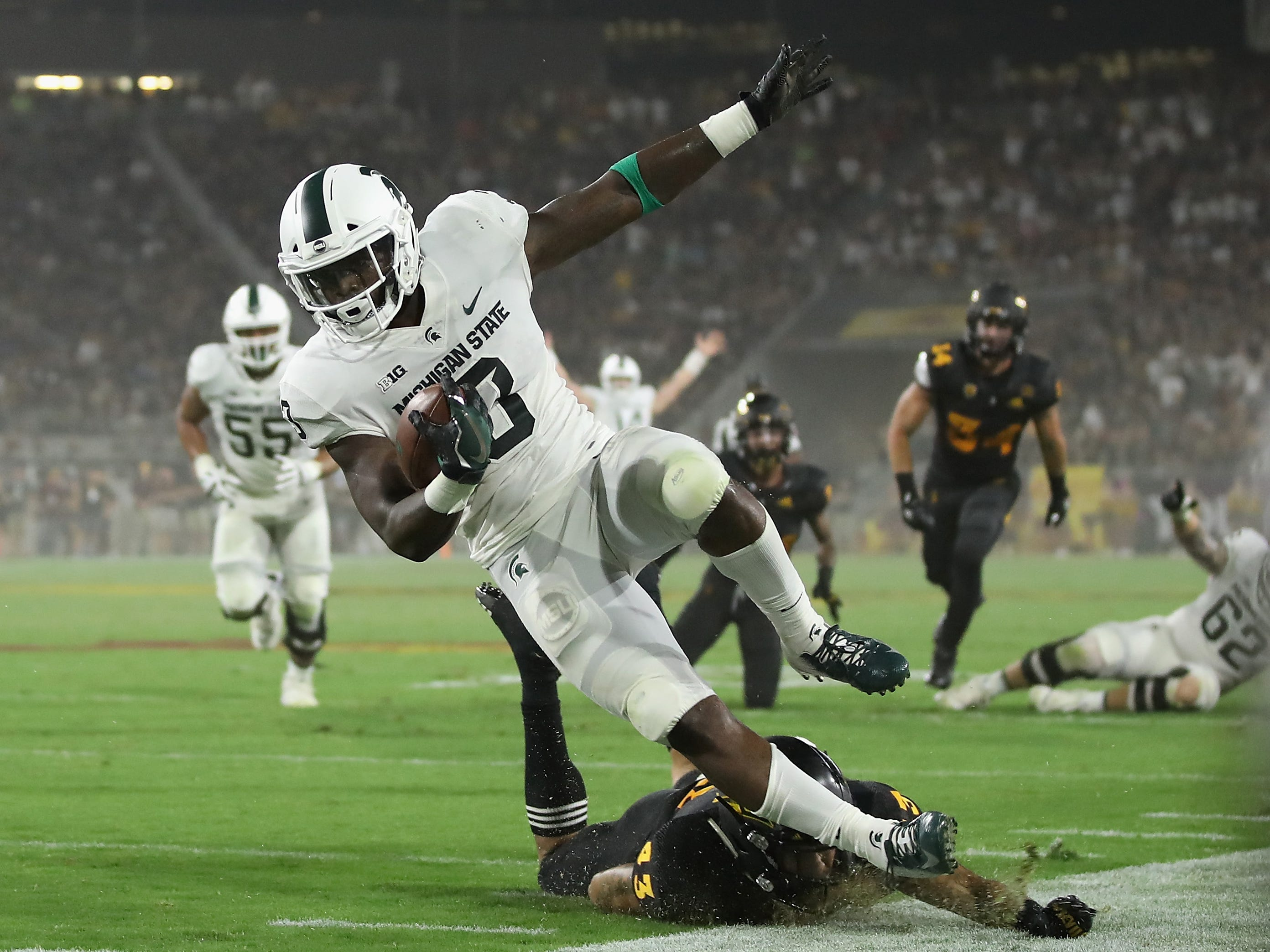 Running back LJ Scott #3 of the Michigan State Spartans is tackled after a reception against the Arizona State Sun Devils during the first half of the college football game at Sun Devil Stadium on September 8, 2018 in Tempe, Arizona.