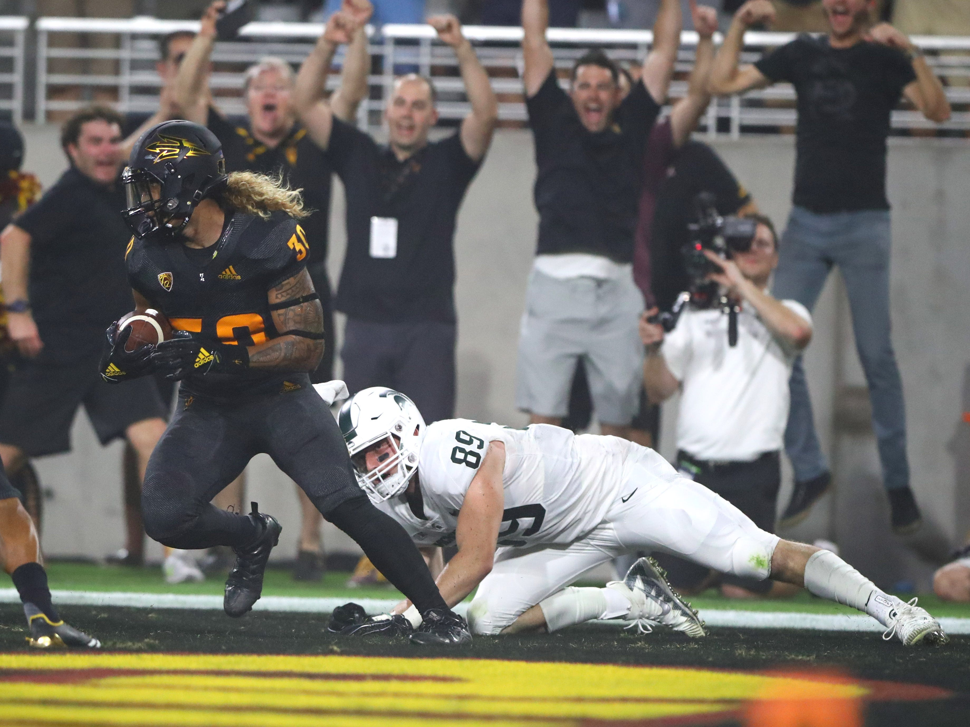 Arizona State Sun Devils defensive back Dasmond Tautalatasi (30) intercepts the ball against Michigan State Spartans tight end Matt Dotson (89) in the first half at Sun Devil Stadium.