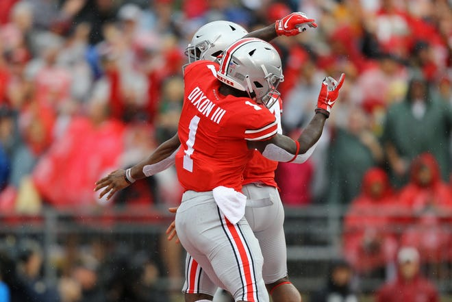 Ohio State receiver Johnnie Dixon celebrates one of his two touchdown catches in Saturday's 52-3 win over Rutgers with fellow wideout Austin Mack.
