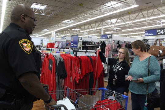 (From left to right) Richland County Sheriff's Office transport officer Chris Allen, 16-year-old Shelbie Colburn of Ontario and Shelbie's grandmother, Amy Milum, consider an Ohio State Buckeyes shirt at Walmart on Sunday, Sept. 9, 2018. The three were taking part in the 22nd annual Cops N Kids.