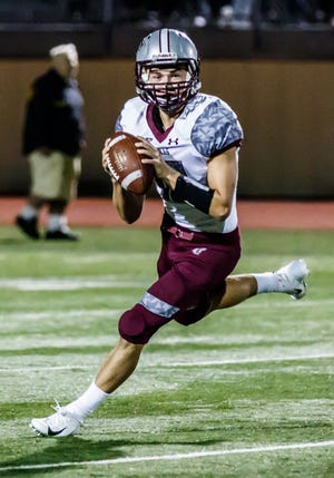 Menomonee Falls senior Logan Larson (12) rolls out to pass during the game against Marquette at Hart Park on Friday, Sept. 7, 2018.