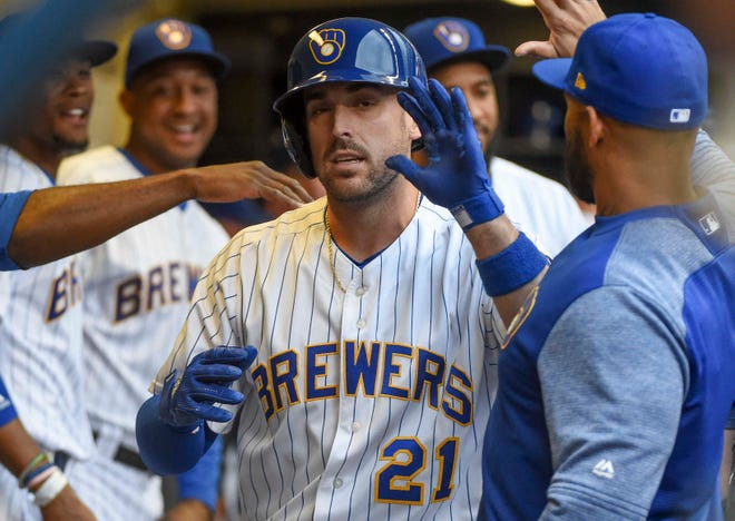 Brewers second baseman Travis Shaw gets a hand from his teammates after a solo homer in the first.