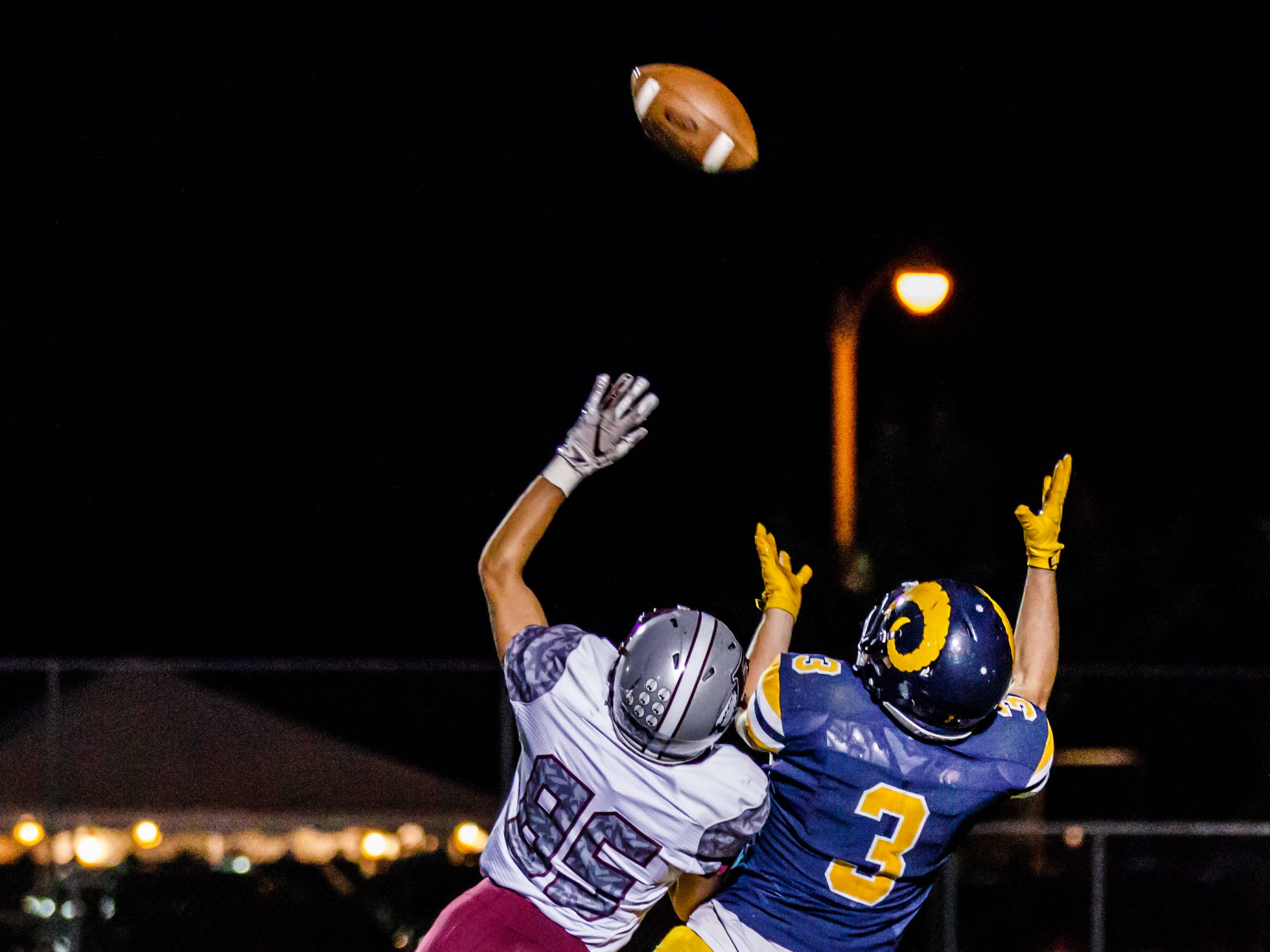 Marquette wide receiver Reed Thompson (3) pulls in a perfectly thrown pass despite a heroic effort by Menomonee Falls defensive back Connor Cedeno (85) at Hart Park on Friday, Sept. 7, 2018. The play was called back due to a holding call on Marquette.