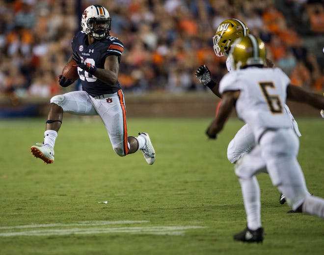Auburn's JaTarvious Whitlow (28) leaps into the air as he runs to the outside against Alabama State at Jordan-Hare Stadium in Auburn, Ala., on Saturday, Sept. 8, 2018. Auburn leads Alabama State 42-2 at halftime.