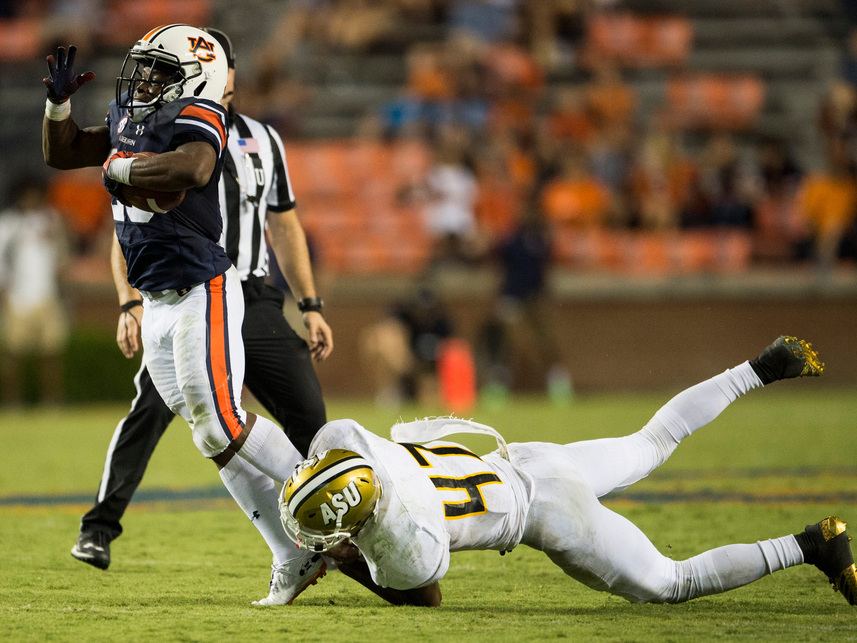 Auburn's Shaun Shivers (25) is tripped up by Alabama State's Kurron Ramsey (47) at Jordan-Hare Stadium in Auburn, Ala., on Saturday, Sept. 8, 2018. Auburn defeated Alabama State 63-9.