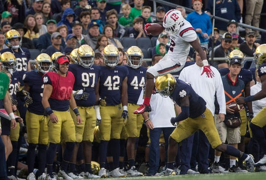 Ball State's Justin Hall leaps over a defender against Notre Dame on Sept. 8, 2018 at Notre Dame Stadium.
