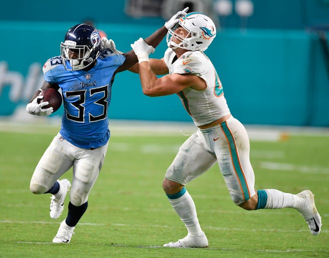 Titans running back Dion Lewis (33) stiff-arms a Miami defender in the fourth quarter Sunday.