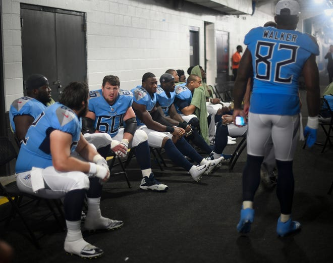 Titans players sit in the hallway outside their locker room during a weather delay during their game against the Dolphins at Hard Rock Stadium Sunday, Sept. 9, 2018, in Miami Gardens, Fla.