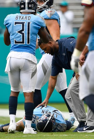 Titans offensive tackle Taylor Lewan (77) is checked out by medical staff after suffering a concussion in the third quarter Sunday.