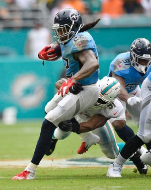 Titans running back Derrick Henry (22) is stopped by a Dolphins defender in the first half Sunday.