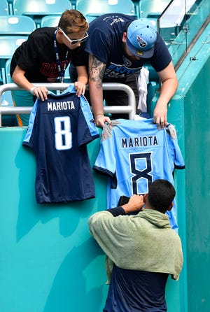 Titans quarterback Marcus Mariota signs autographs for fans before the game against the Dolphins on Sunday at Hard Rock Stadium.