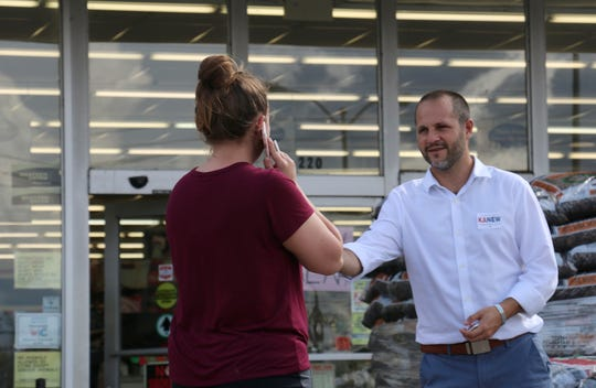 Democratic candidate Justin Kanew hands a Selmer resident his card while campaigning in the Piggly Wiggly parking lot in Selmer, Tennessee, on Sept. 7, 2018.