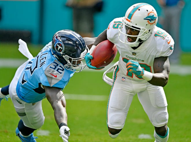 The Titans' David Fluellen (32) tackles the Dolphins' Jakeem Grant (19) on a punt return in the weather-delayed second quarter Sunday.