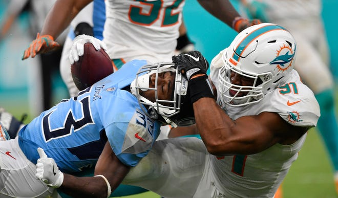 Titans running back Dion Lewis (33) is tackled in the third quarter by Dolphins defensive tackle Jordan Phillips.