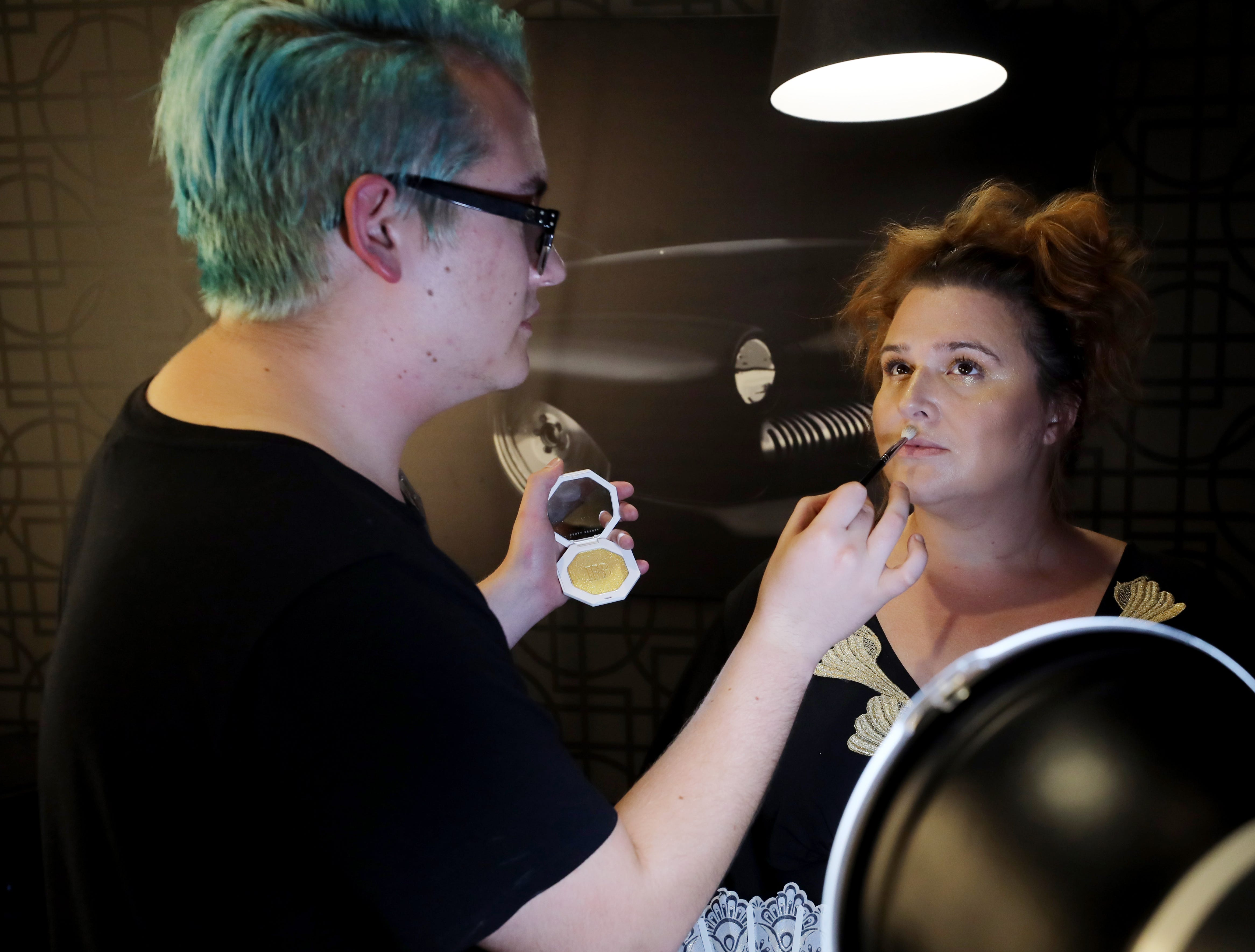 Gunnar Lundblad, left, applies makeup for Heidi Oechsel before the start of the Boundless 2018 fashion show held at Studio 615 on Saturday September 8, 2018.
