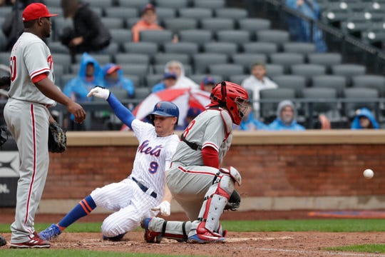 New York Mets Brandon Nimmo (9) slides safely into home as Philadelphia Phillies catcher Jorge Alfaro waits for the throw in the seventh inning of a baseball game, Sunday, Sept. 9, 2018, in New York. Phillies pitcher Hector Neris, left, watches the play. Nimmo scored from first on a double by Austin Jackson. The Mets won 6-4. (AP Photo/Mark Lennihan)