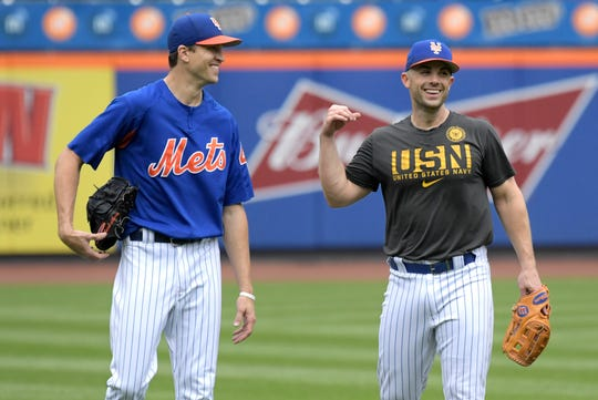 New York Mets' David Wright, right, walks off the field with Jacob deGrom, left, after playing in a simulated baseball game Saturday, Sept. 8, 2018, in New York.
