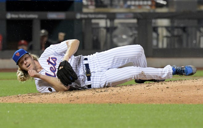 New York Mets pitcher Noah Syndergaard hits the dirt after being hit on the ribs by a ball hit by Philadelphia Phillies' Cesar Hernandez during the seventh inning of a baseball game Saturday, Sept. 8, 2018 in New York. Syndergaard had to leave the game.
