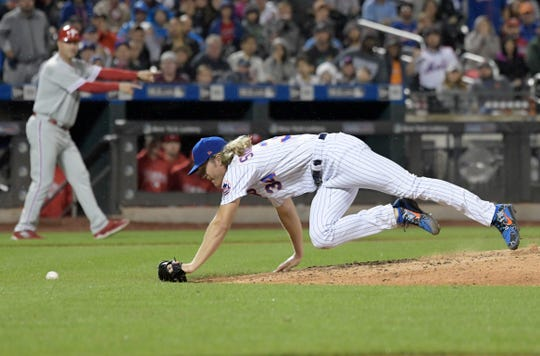 New York Mets pitcher Noah Syndergaard scrambles after a ball hit by Philadelphia Phillies' Cesar Hernandez during the seventh inning of a baseball game Saturday, Sept. 8, 2018, in New York.