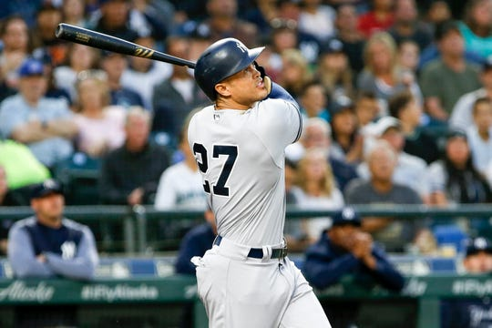 Sep 8, 2018; Seattle, WA, USA; New York Yankees designated hitter Giancarlo Stanton (27) hits an RBI sacrifice fly against the Seattle Mariners during the fifth inning at Safeco Field.