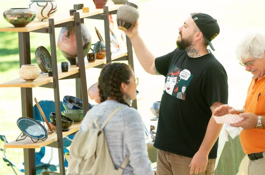 Chris Alvarado, of Las Cruces, checks out handmade items from Pachamama Pottery on Saturday, September 8, 2018 during Monuments to Main Street at Klein Park.