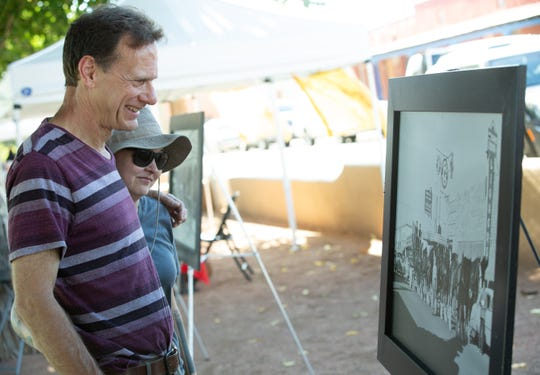 Steve McGee and Carla Deemer look at historic photos of downtown Las Cruces that are on display on Saturday, September 8, 2018 during Monuments to Main Street at Klein Park.