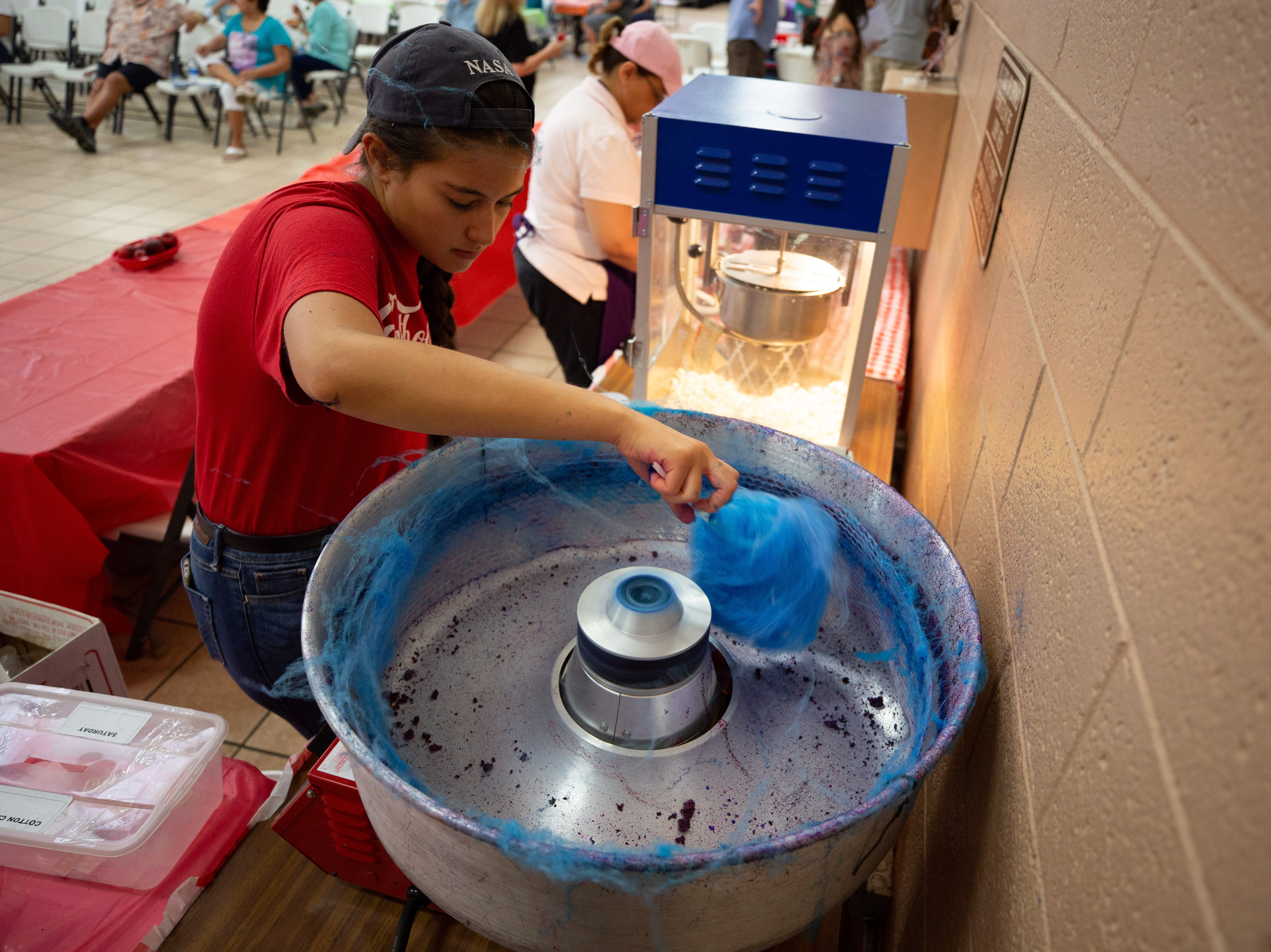 Cotton candy maker Olivia Pina, 15, makes a blue cotton candy for a customer at the St. Genevieve Fiesta on Saturday, Sept. 8, 2018.
