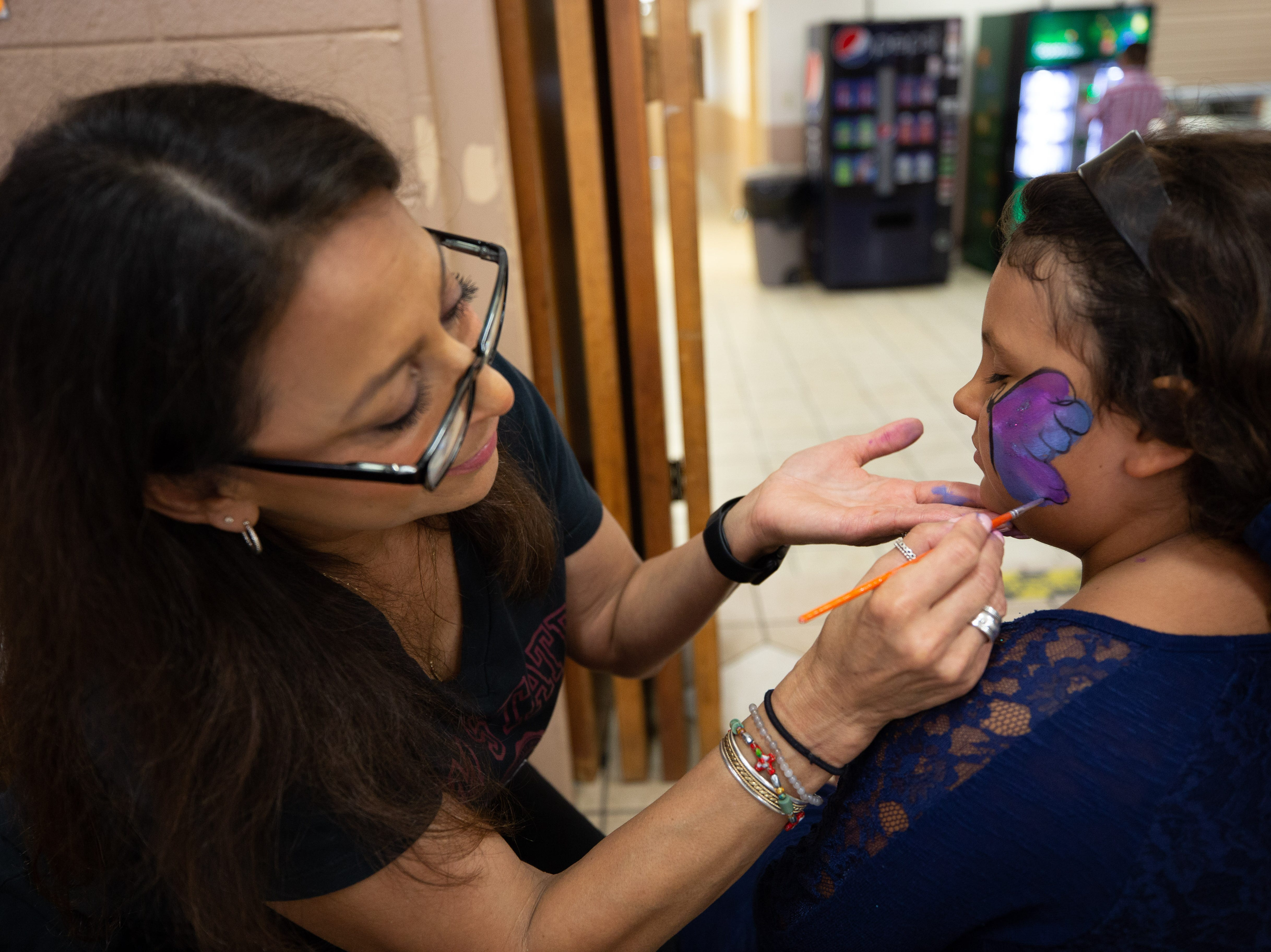 Bendi Saucedo, 7, sits still as Cindy Salas paints a colorful design on her cheek at the St. Genevieve Fiesta on Saturday, Sept. 8, 2018.