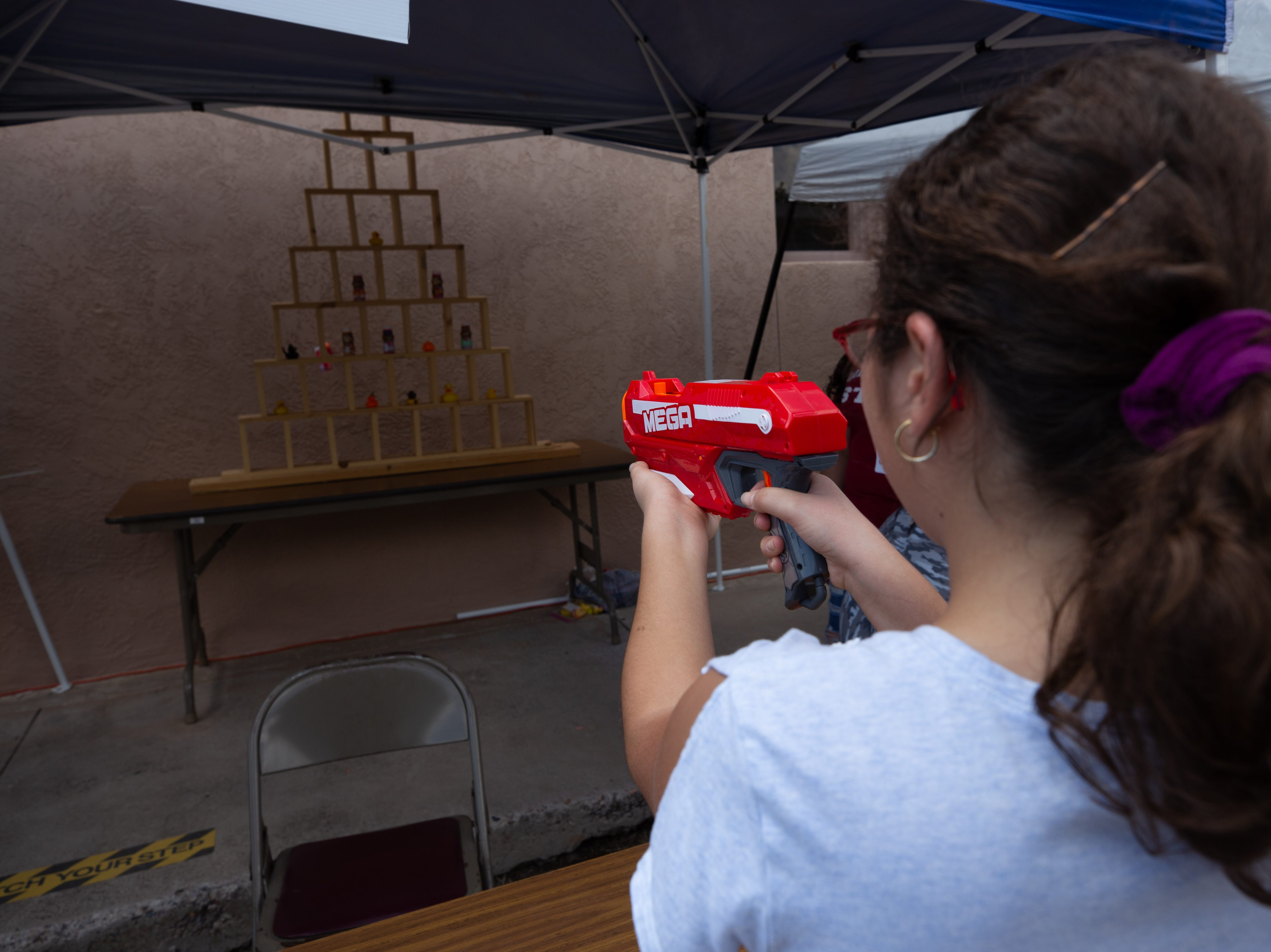Sara Schmitz, 12, takes aim with her dart gun at the prize wall during the St. Genevieve Fiesta on Saturday, Sept. 8, 2018.