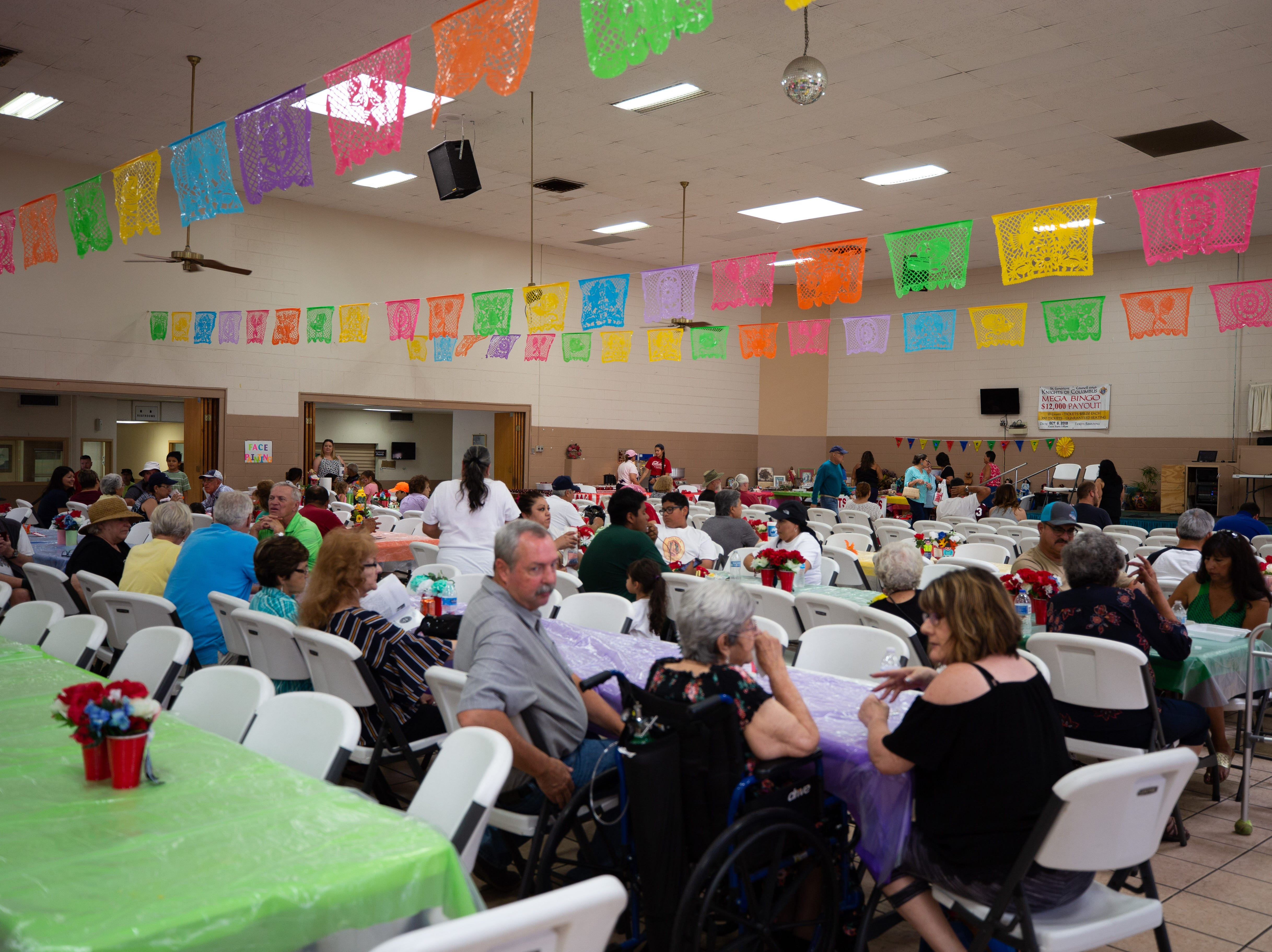 Fiesta attendees relax in the cool comfort of the parish hall at the St. Genevieve Fiesta on Saturday, Sept. 8, 2018.
