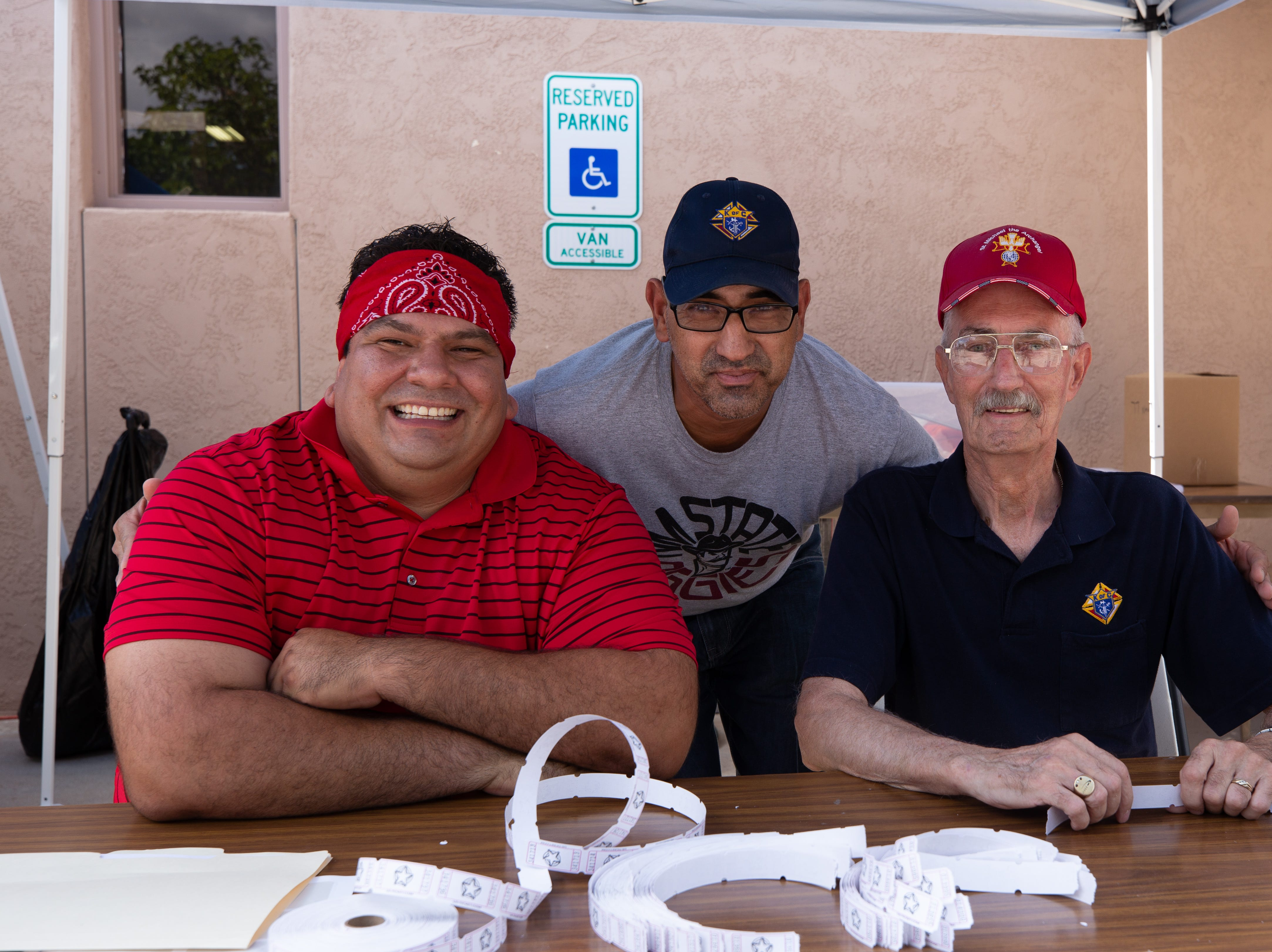 Knights of Columbus Council 13969 members, from left, Joaquin Silva, Alberto Grijalva and Kerri Morley, sell game tickets at the St. Genevieve Fiesta on Saturday, Sept. 8, 2018.