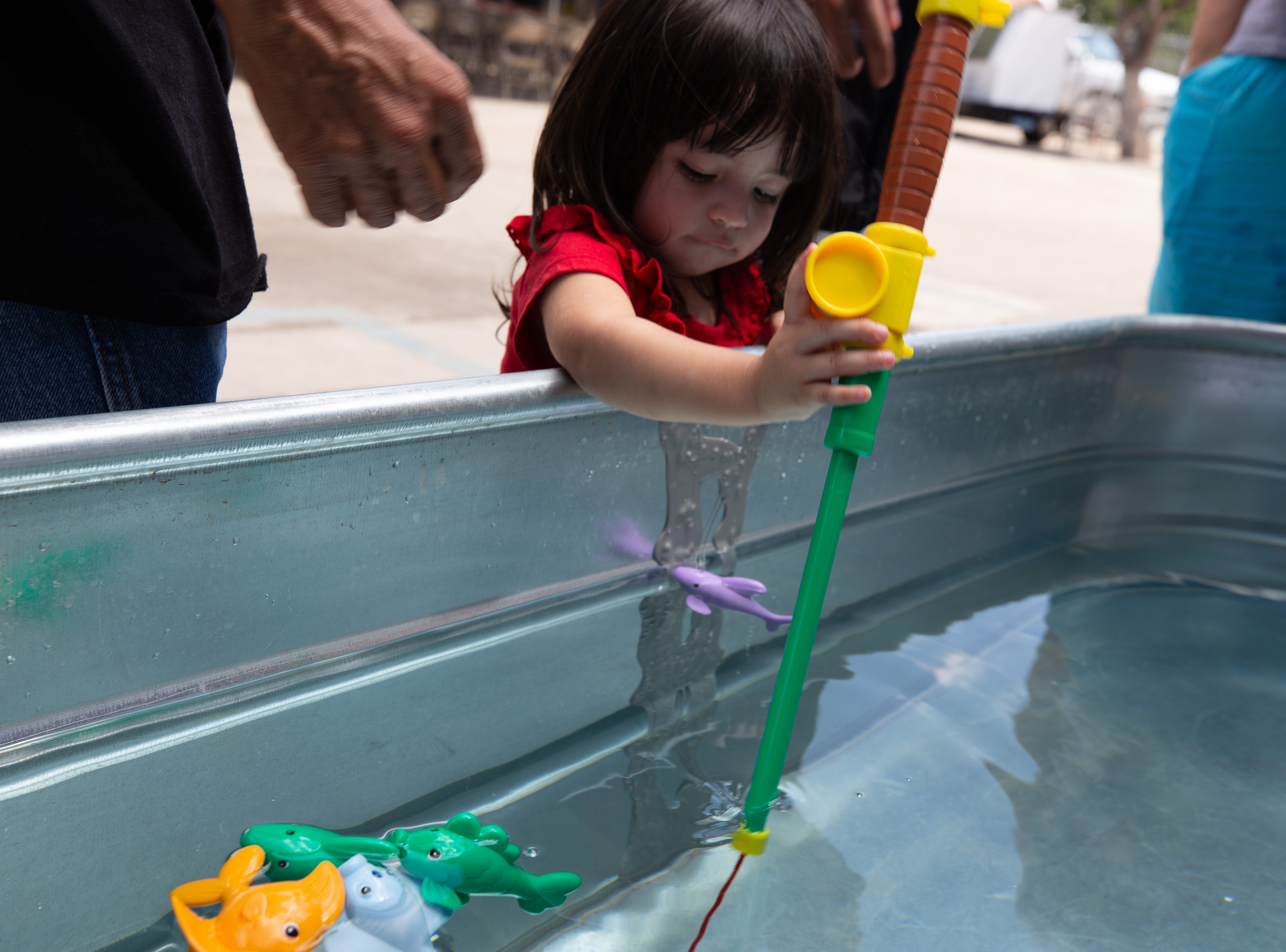 Josephine Gallardo, 2, tries an unconventional method of catching a plastic fish at the St. Genevieve Fiesta on Saturday, Sept. 8, 2018.