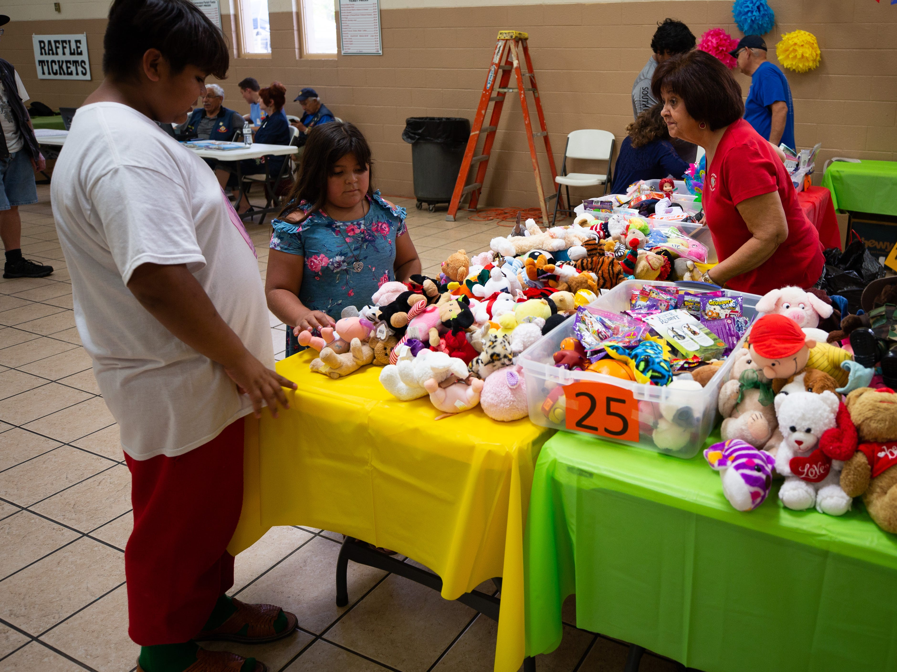 """Mary Tellez assists Ylai Zavala, 13, and Azul Ramos, 9, who spend their """"ticket money"""" on toys and stuffed animals at the St. Genevieve Fiesta on Saturday, Sept. 8, 2018."""