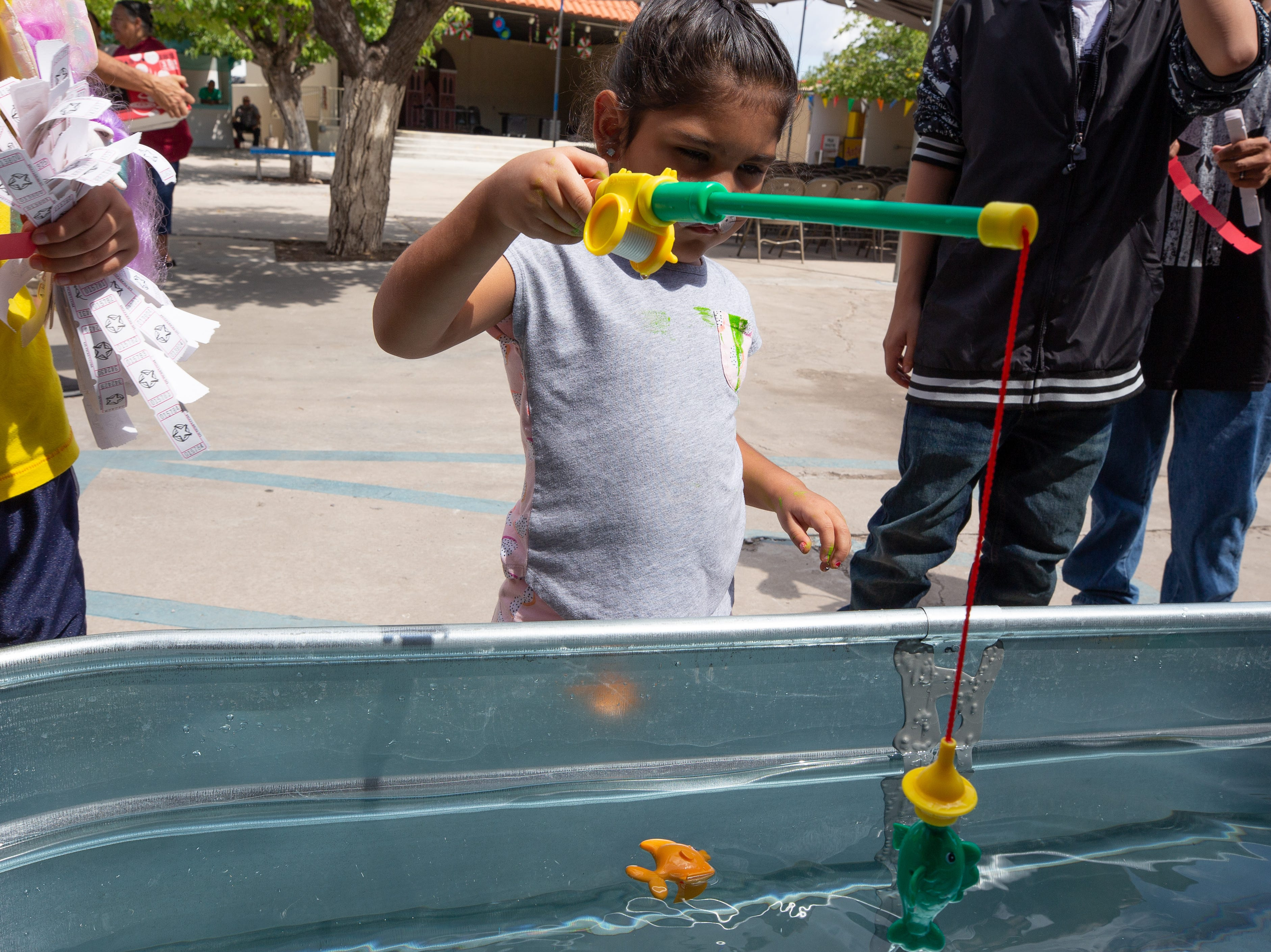 Camila Nuñez, 4, reels in her fish at the fishing pond booth at the St. Genevieve Fiesta on Saturday, Sept. 8, 2018.