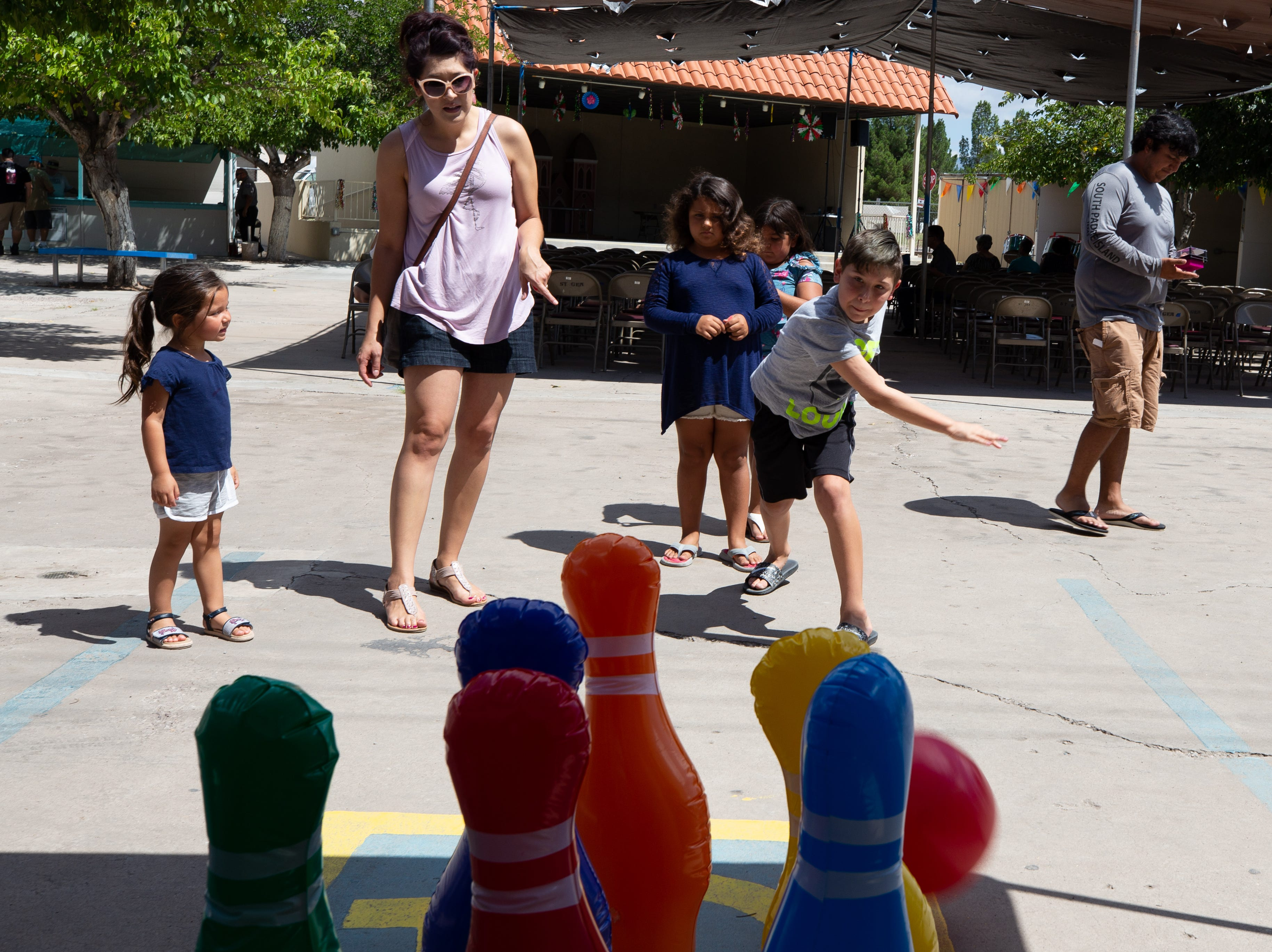 Noah Ferda, 10, flings a bowling ball at inflatable pins as his mother Karrie Espinosa and sister Mia, 3, look on at the St. Genevieve Fiesta on Saturday, Sept. 8, 2018.