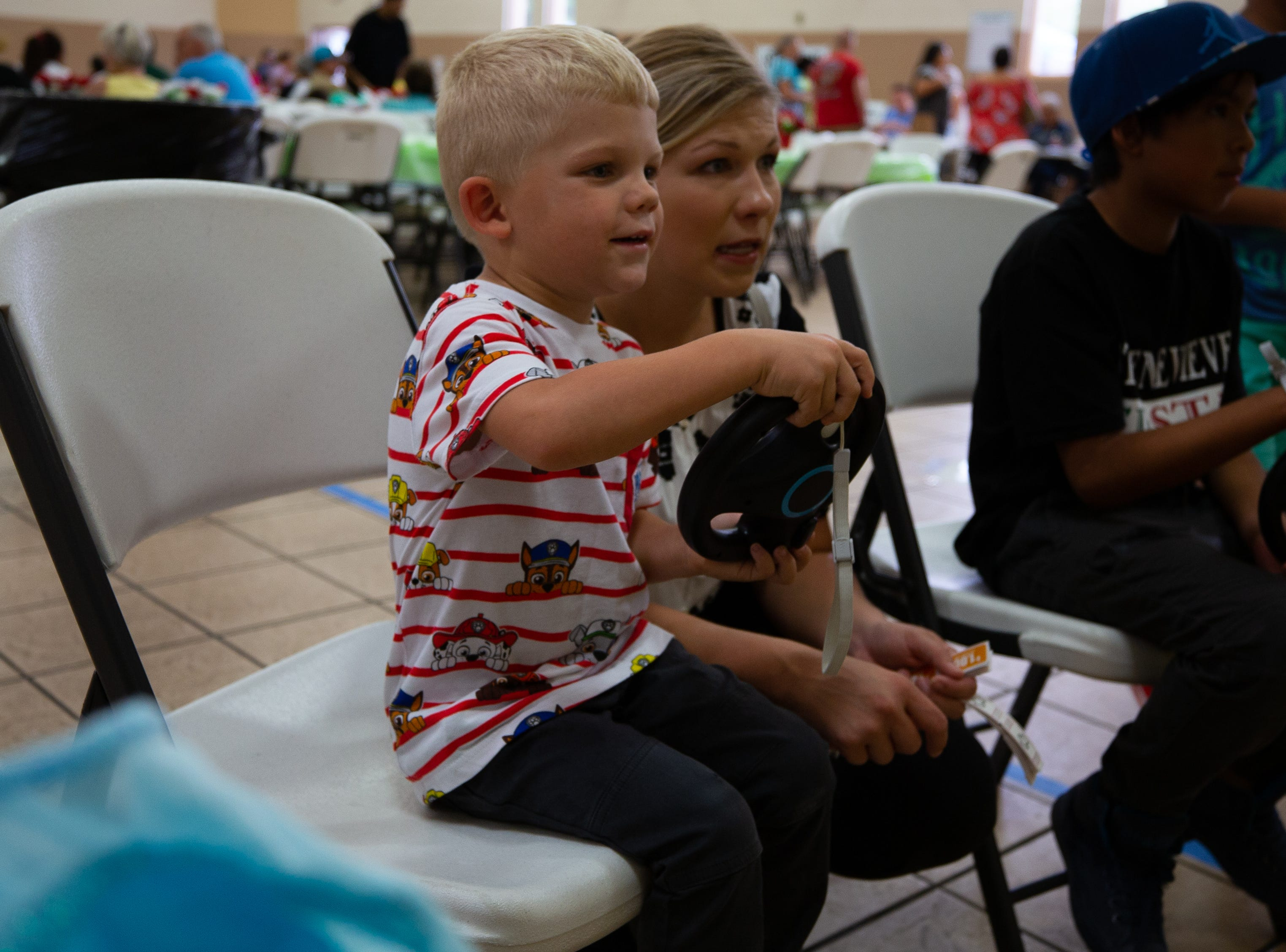 Connor Campbell, 4, concentrates on driving his Wii car while his mother Brittany looks on at the St. Genevieve Fiesta on Saturday, Sept. 8, 2018.
