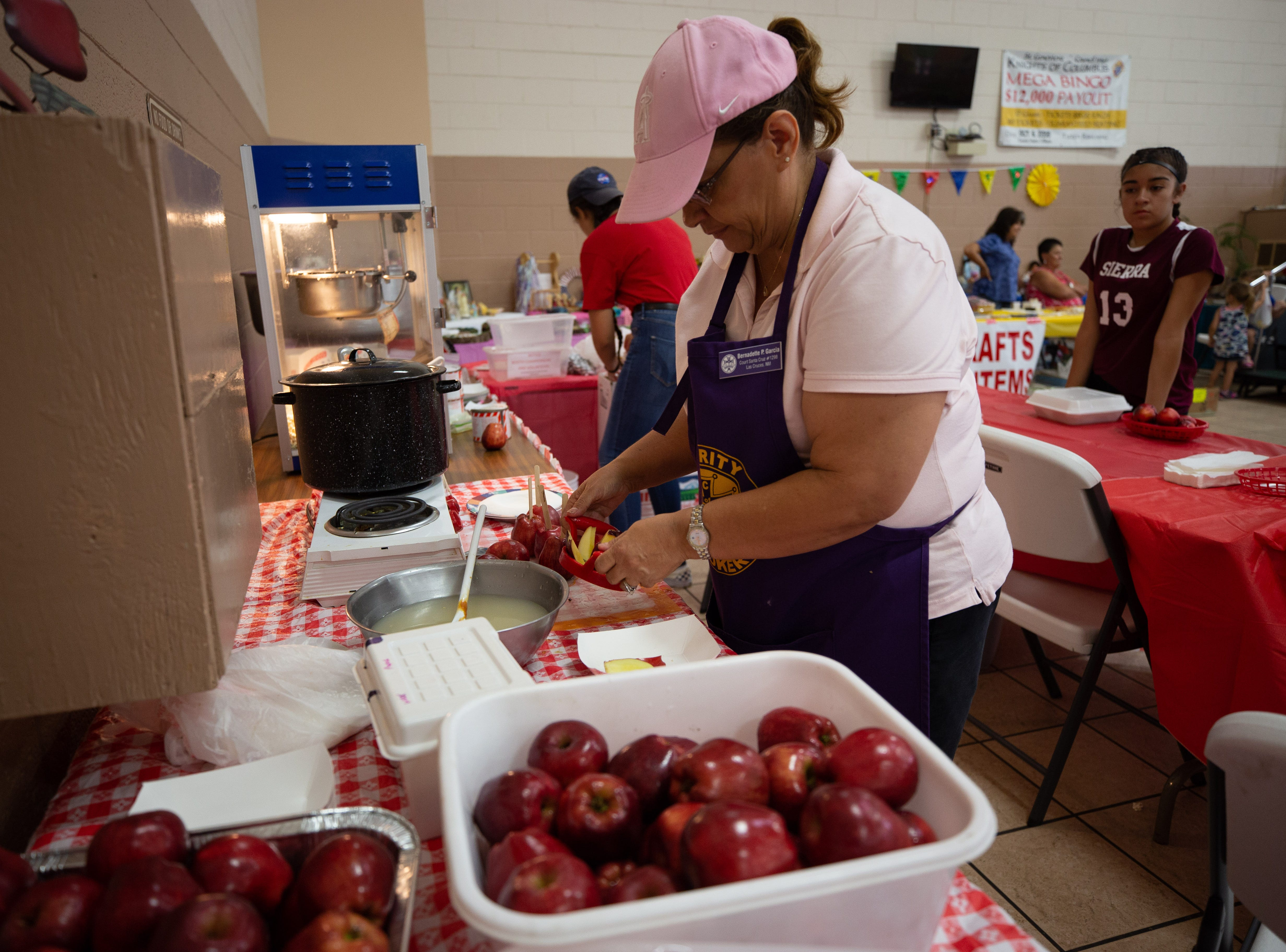 Bernadette Garcia prepares apples for a caramel drizzle at the St. Genevieve Fiesta on Saturday, Sept. 8, 2018.