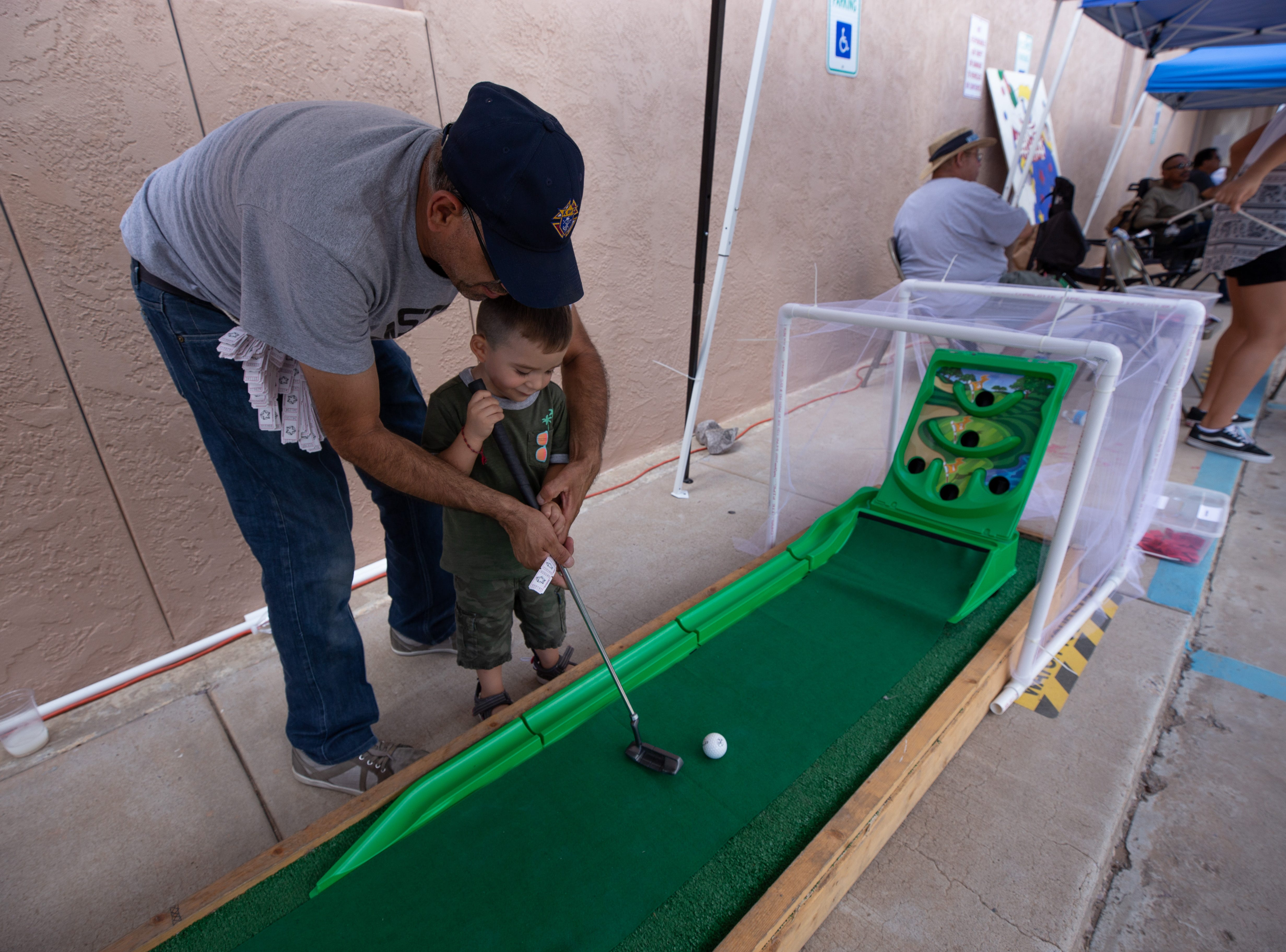 Alberto Grijalva assists Xmael Vargas, 2, with his golf swing during the St. Genevieve Fiesta on Saturday, Sept. 8, 2018.