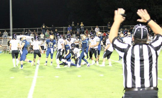 The Warriors and the Tigers scramble on the field trying to gain possession of the ball.
