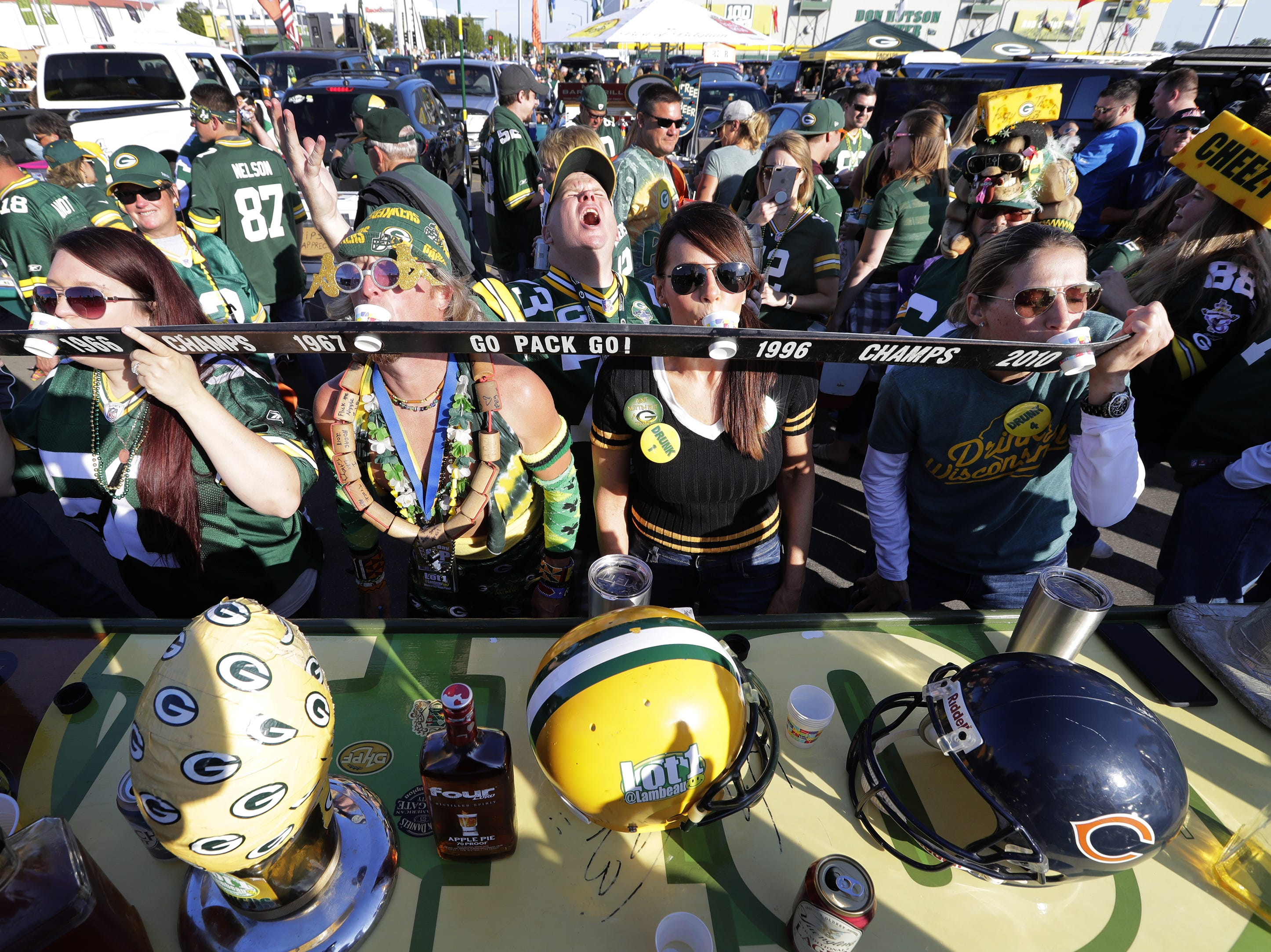 Football fans down shots while tailgating prior to the Green Bay Packers playing the Chicago Bears Sunday, Sept. 9, 2018, at Lambeau Field in Green Bay, Wis.