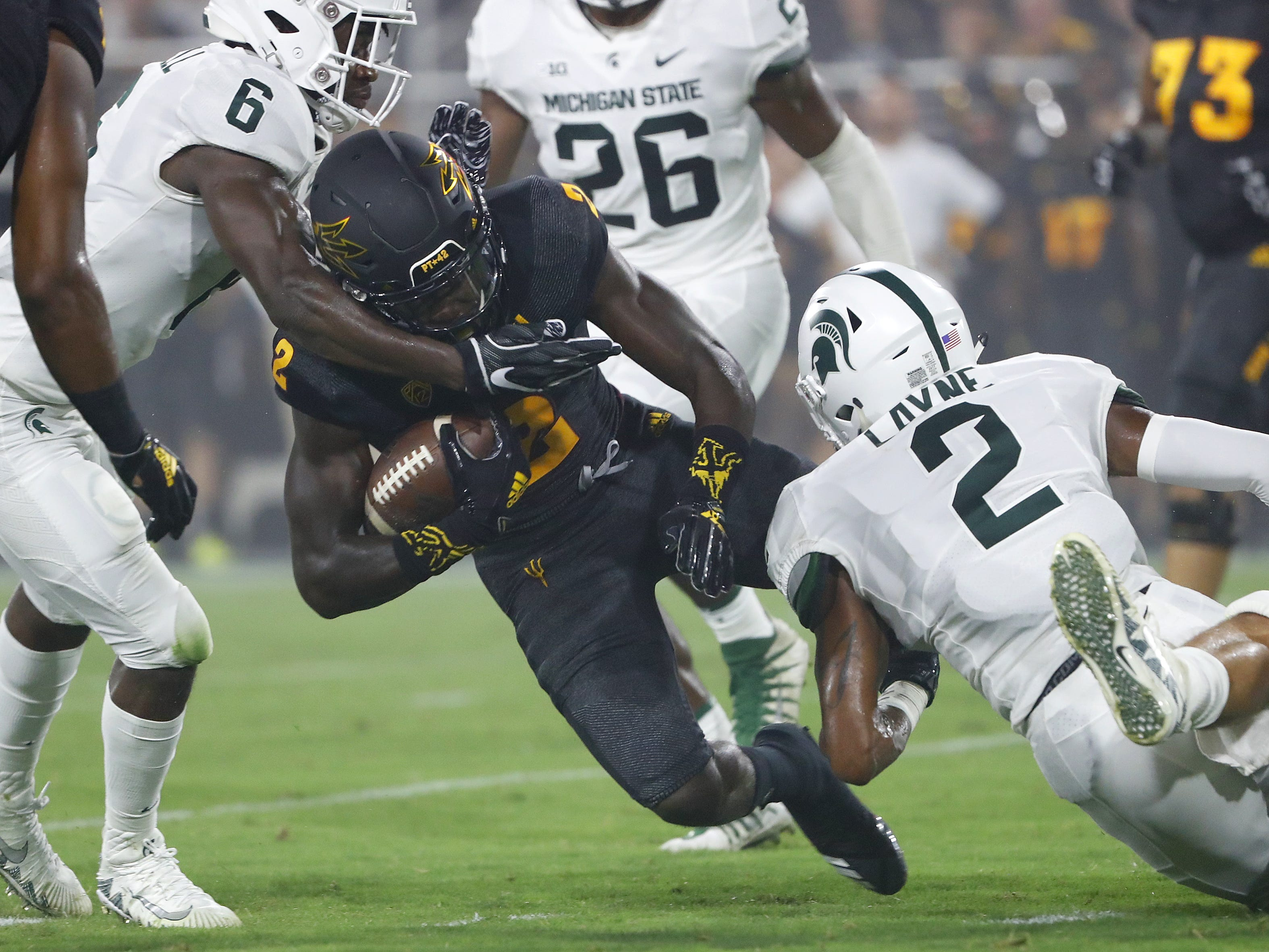 Michigan State's David Dowell (6) and Justin Layne (2) tackle Arizona State Sun Devils wide receiver Brandon Aiyuk (2) during the first quarter at Sun Devil Stadium in Tempe, Ariz. on Sept. 8, 2018.