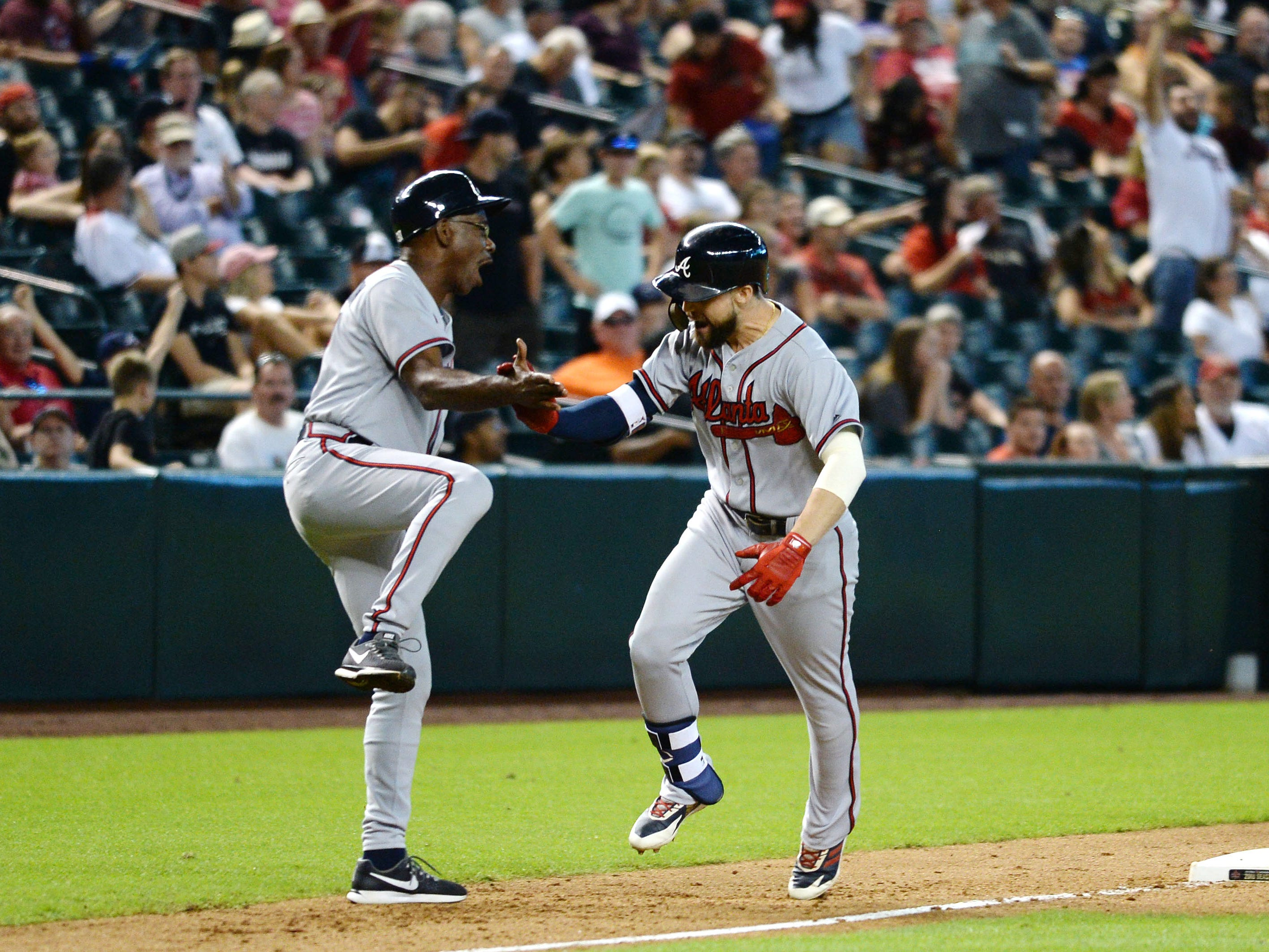 Sep 9, 2018; Phoenix, AZ, USA; Atlanta Braves center fielder Ender Inciarte (right) slaps hands with third base coach Ron Washington (left) after hitting a three run home run against the Arizona Diamondbacks during the ninth inning at Chase Field.