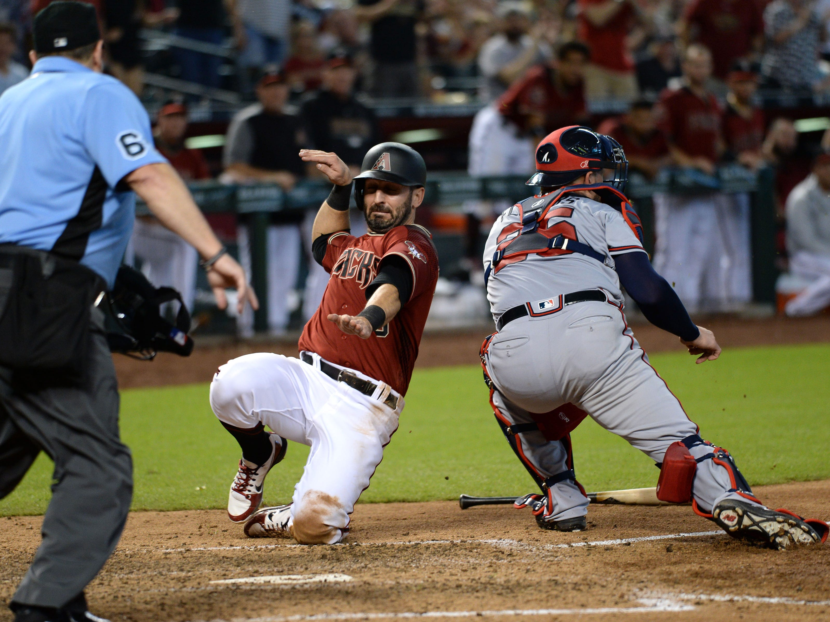 Sep 9, 2018; Phoenix, AZ, USA; Arizona Diamondbacks third baseman Daniel Descalso (3) slides at home plate ahead of the tag of Atlanta Braves catcher Tyler Flowers (25) to score a run during the sixth inning at Chase Field.