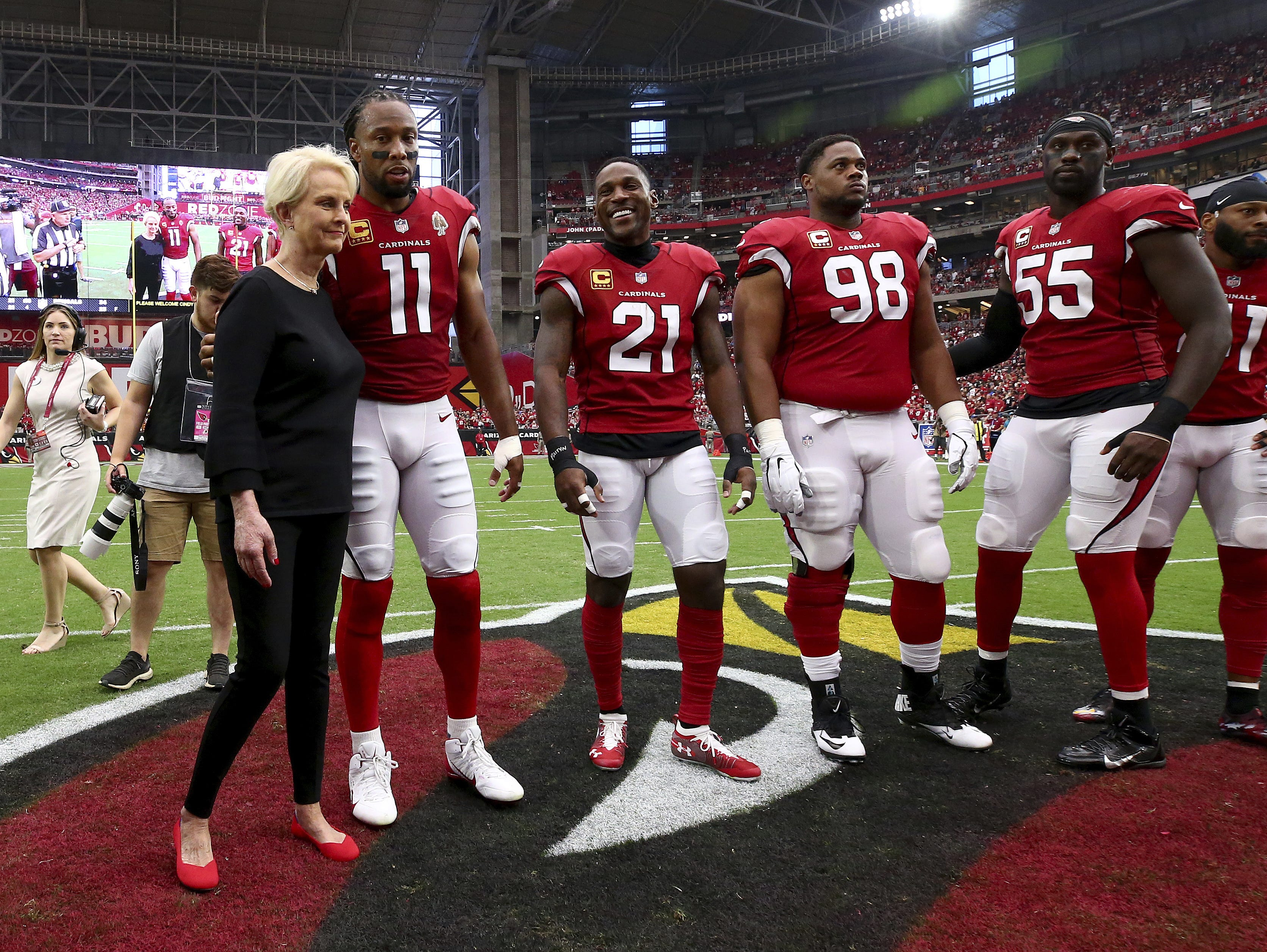 Cindy McCain, wife of the late U.S. Sen. John McCain, R-Ariz., embraces Arizona Cardinals' Larry Fitzgerald (11), Patrick Peterson (21), Corey Peters (98) and Chandler Jones (55) as an honorary team captain during the coin toss prior to an NFL football game against the Washington Redskins , Sunday, Sept. 9, 2018, in Glendale, Ariz. Rob Schumacher/The Republic