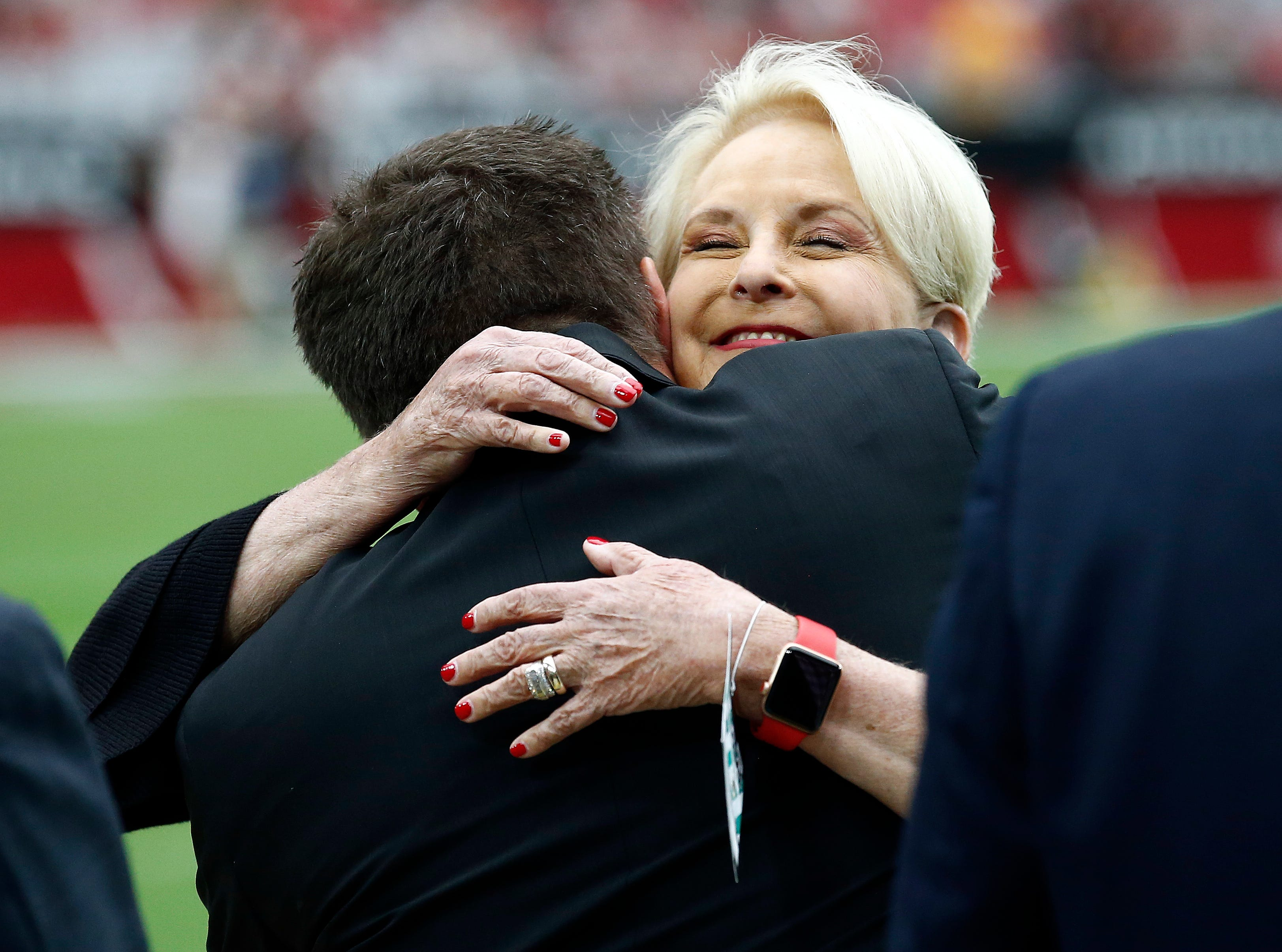 Cindy McCain, wife of the late U.S. Sen. John McCain, embraces Arizona Cardinals president Michael Bidwill prior to an NFL football game between the Washington Redskins and the Arizona Cardinals, Sept. 9, 2018, in Glendale, Ariz.