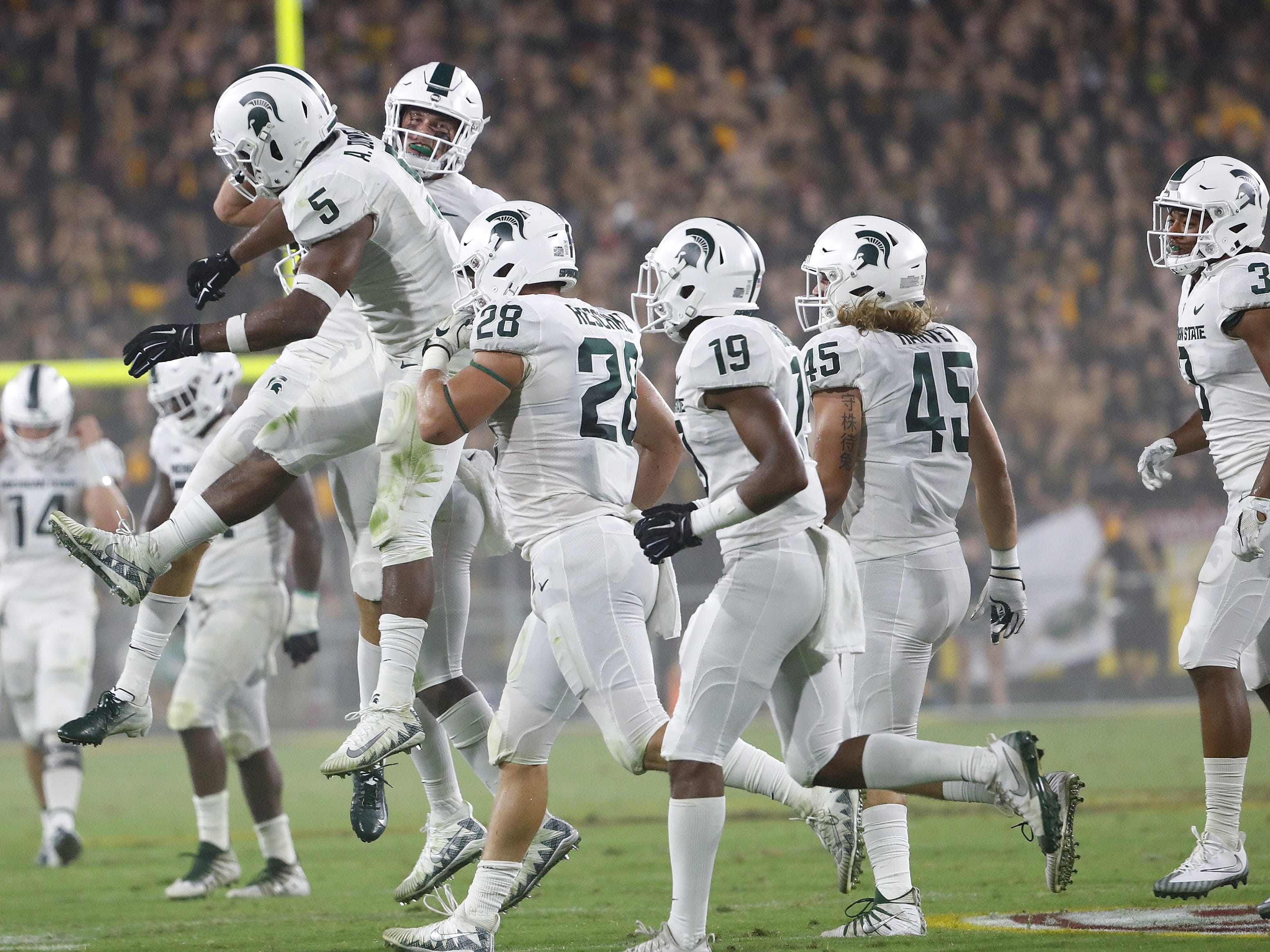 Michigan State's Matt Morrissey (10) jumps into teammate Andrew Dowell (5) after recording an interception during the second quarter at Sun Devil Stadium in Tempe, Ariz. on Sept. 8, 2018.